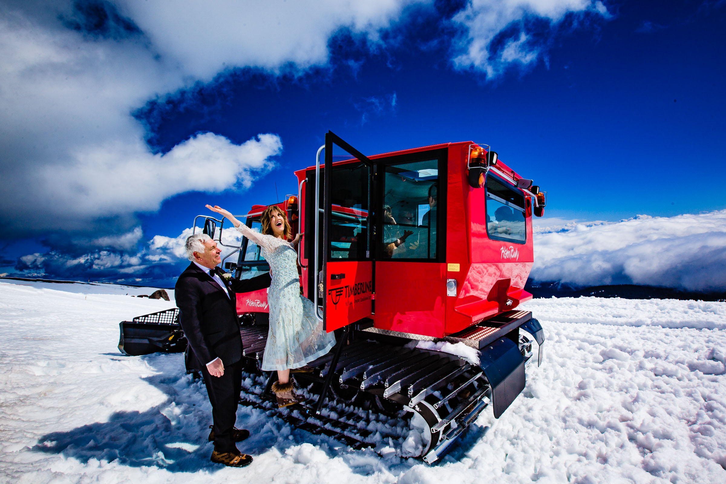 Bride and groom enjoying the snow cat ride up to Silcox Hut for their Timberline Lodge Elopement on a beautiful sunny blue sky day