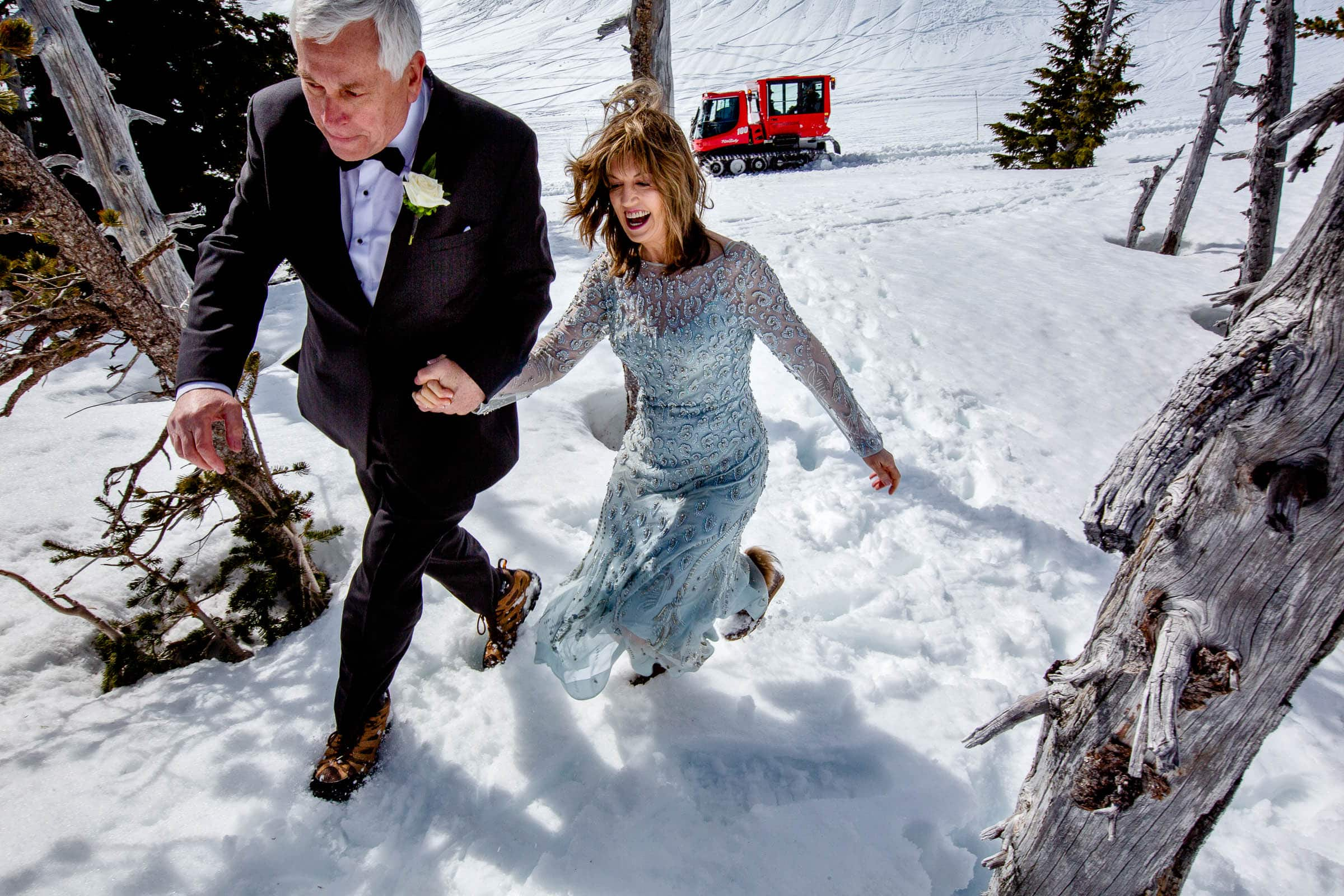 Action shot of bride and groom running hand and hand up the mountain near Silcox Hut for their Timberline Lodge elopement on Mt Hood.