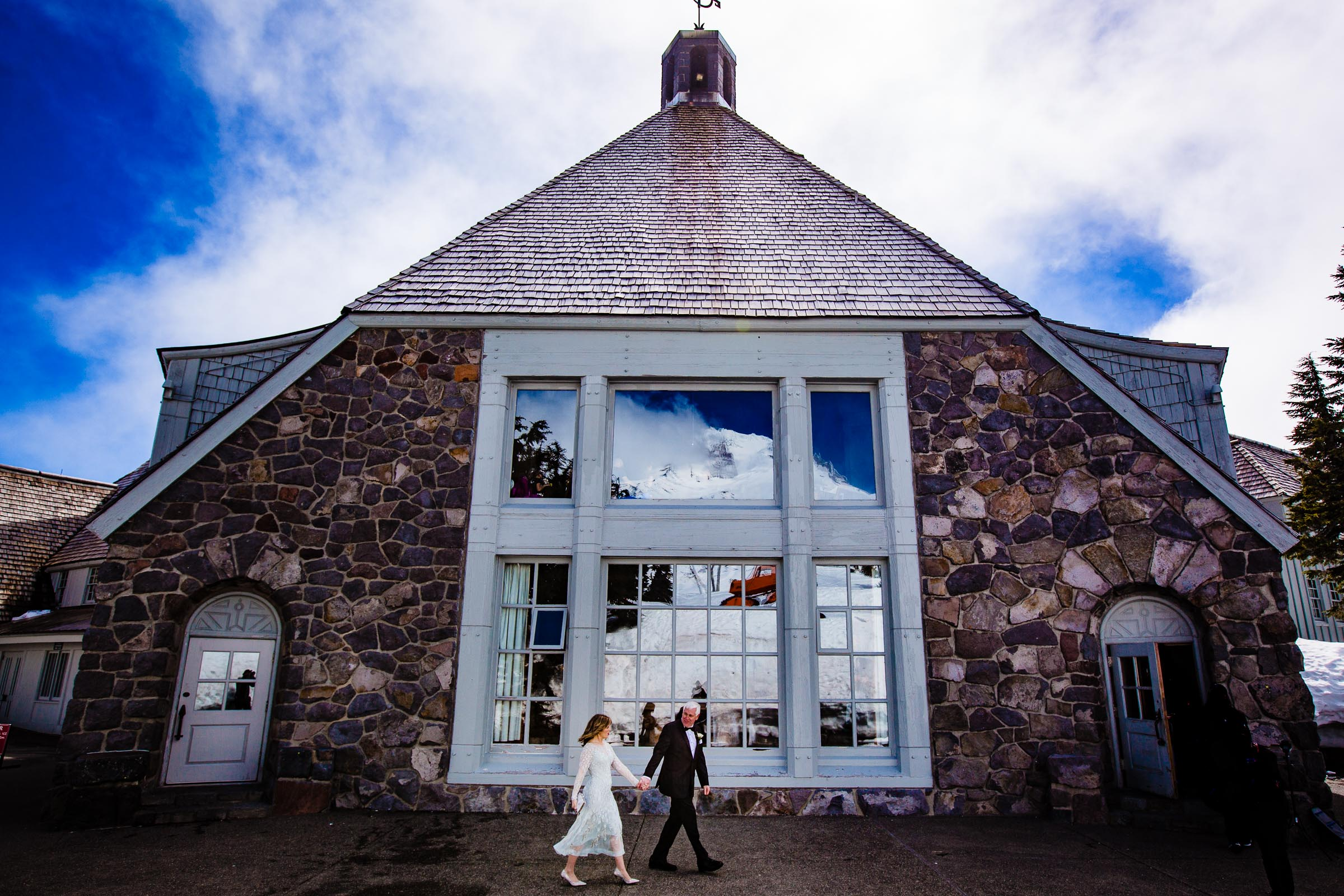 Bride and groom walking outside Timberline Lodge infront of the big windows before their Timberline Lodge Elopement