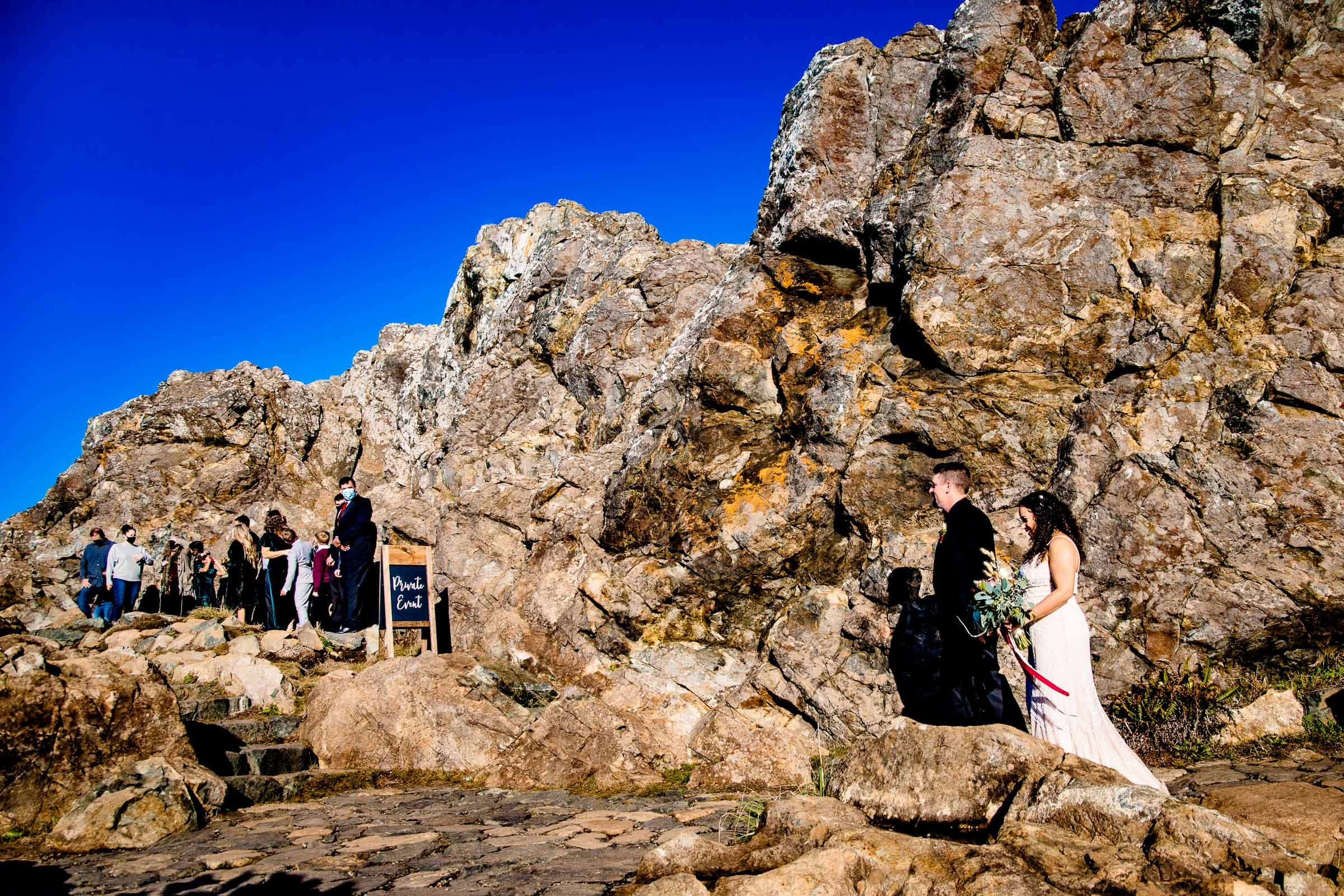 Bride and groom walking on Wedding Rock into their Trinidad elopement ceremony near Humboldt California