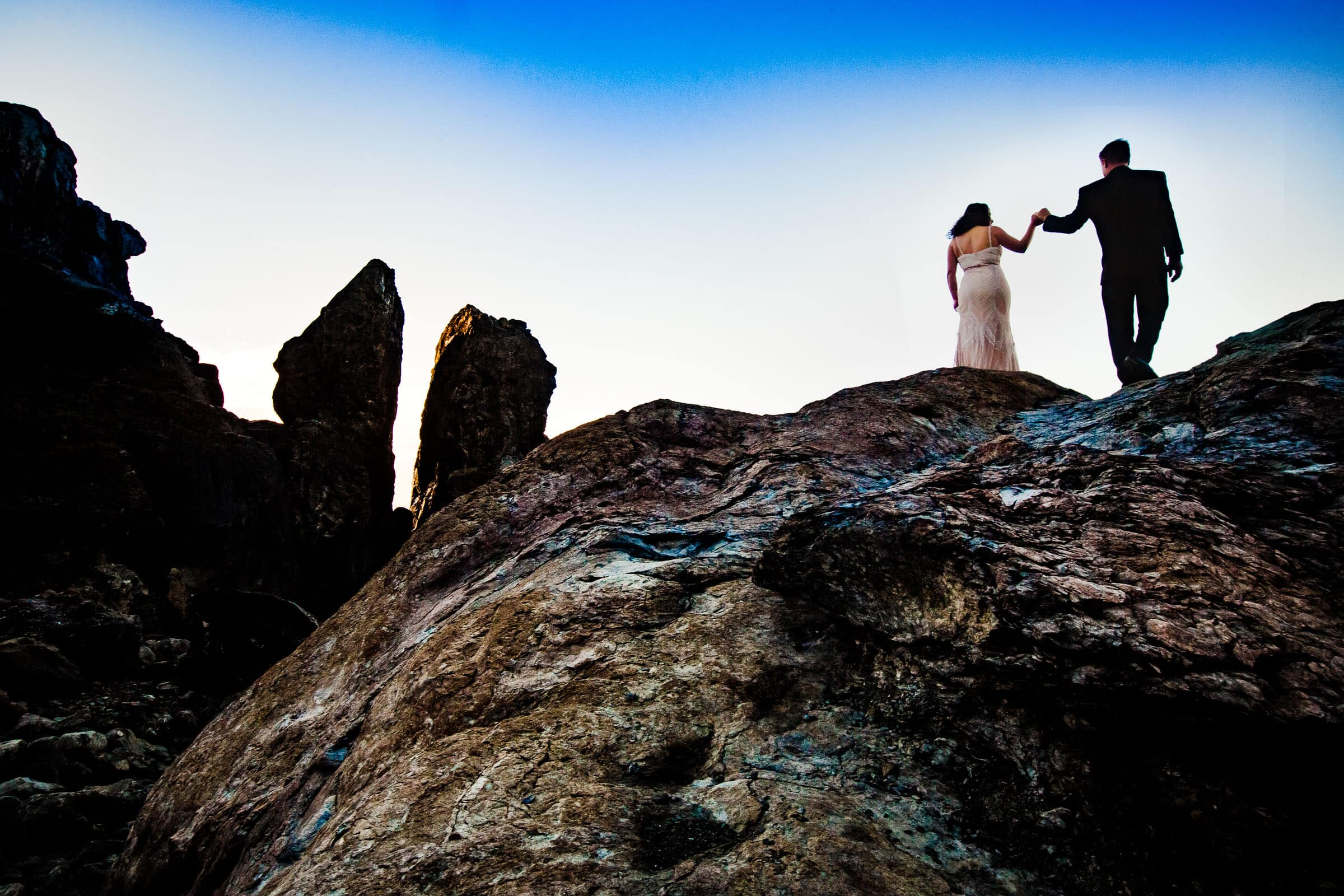 Bride and groom walking up Wedding Rock for their Patricks Point elopement at sunset