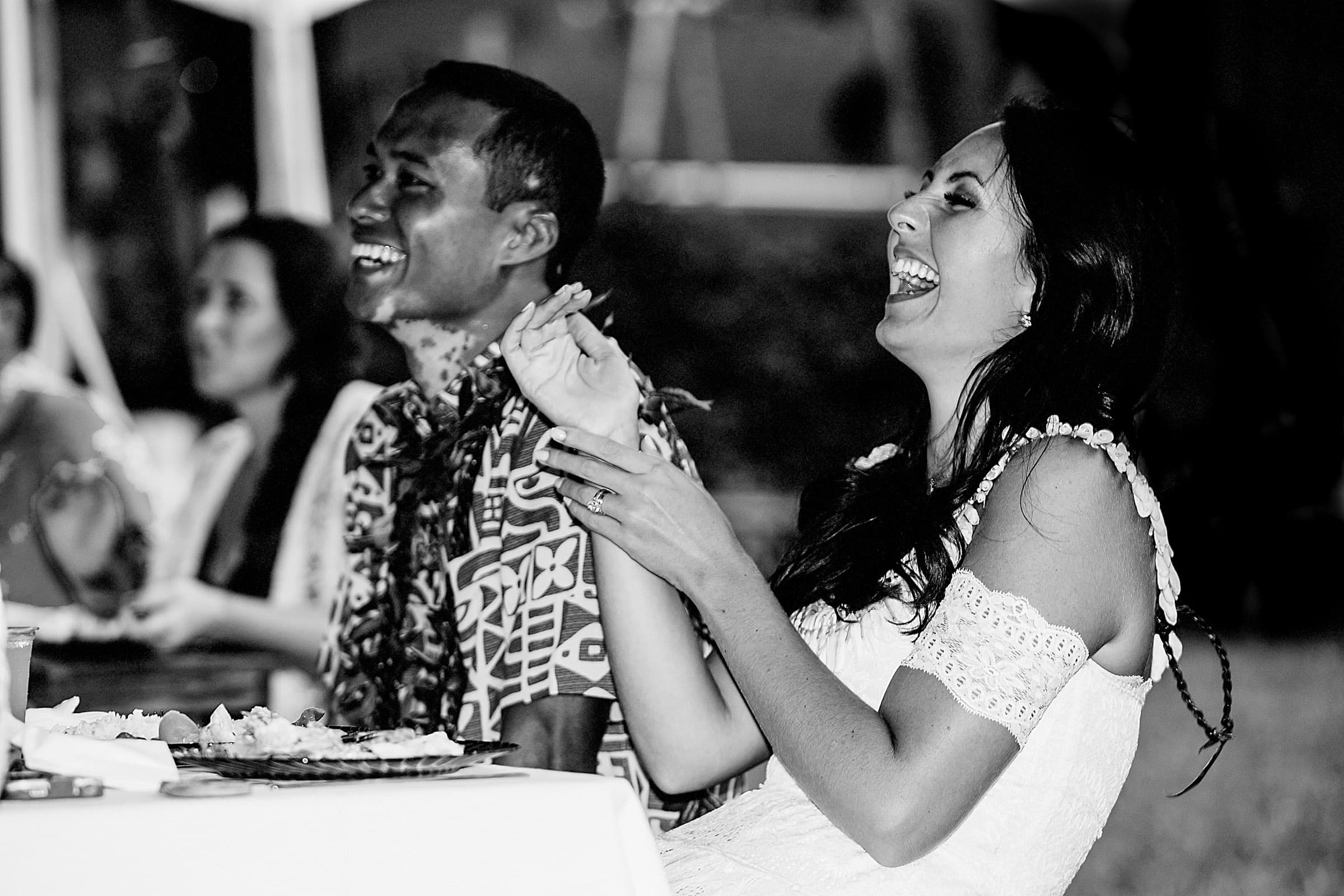 Bride laughing during speeches at a Kauai Island wedding amidst massive majestic acacias trees on a private estate
