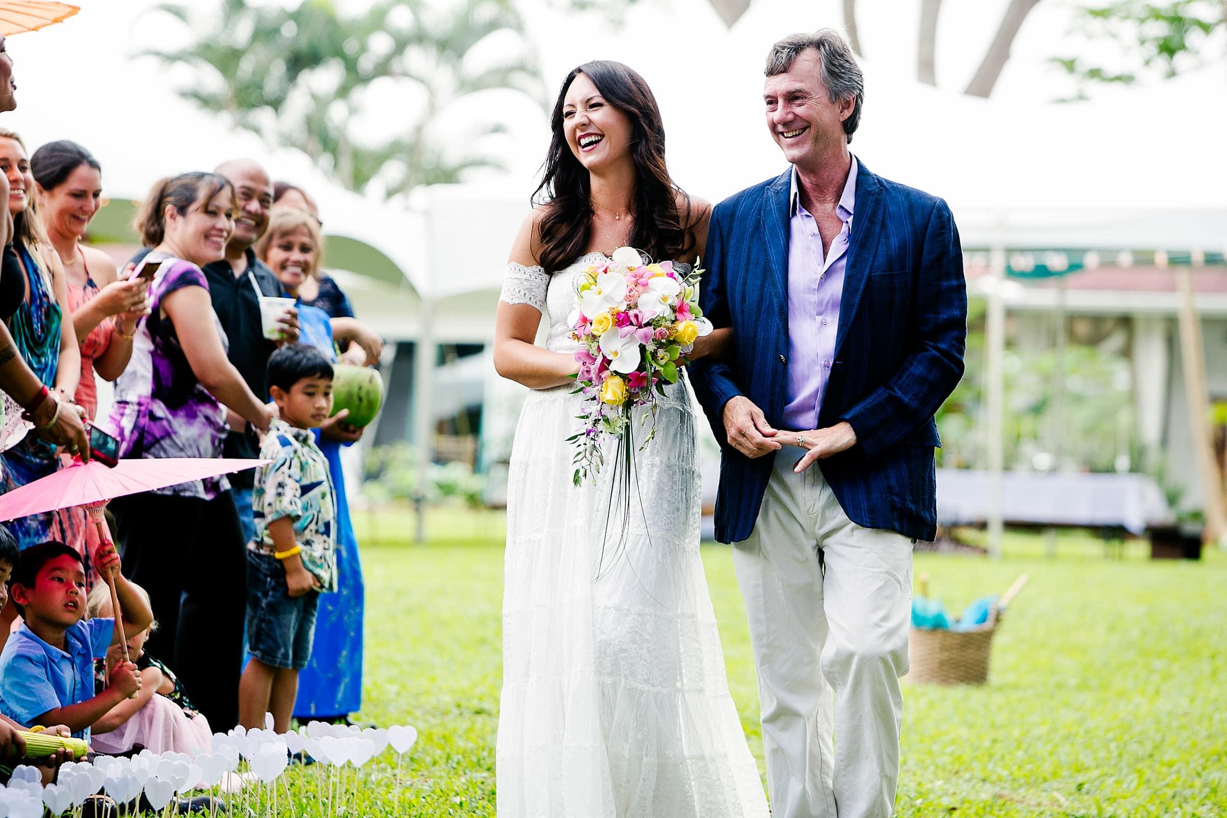A happy bride walking into her Kauai Island wedding ceremony amidst massive majestic acacias trees on a private estate
