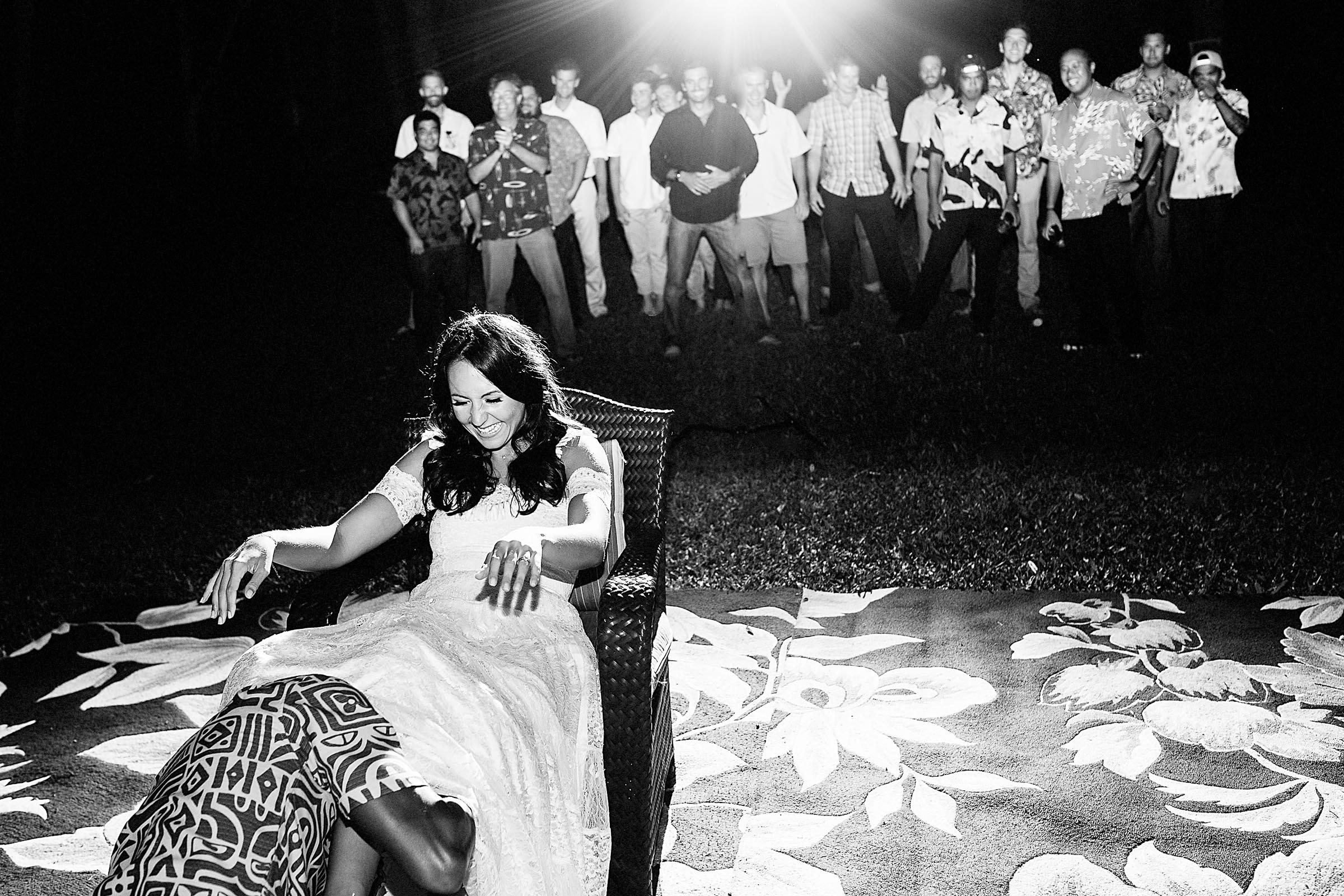 Fun photo of a bride in a chair with her groom taking her garter off during their Kauai Island wedding reception amidst massive majestic acacias trees on a private estate