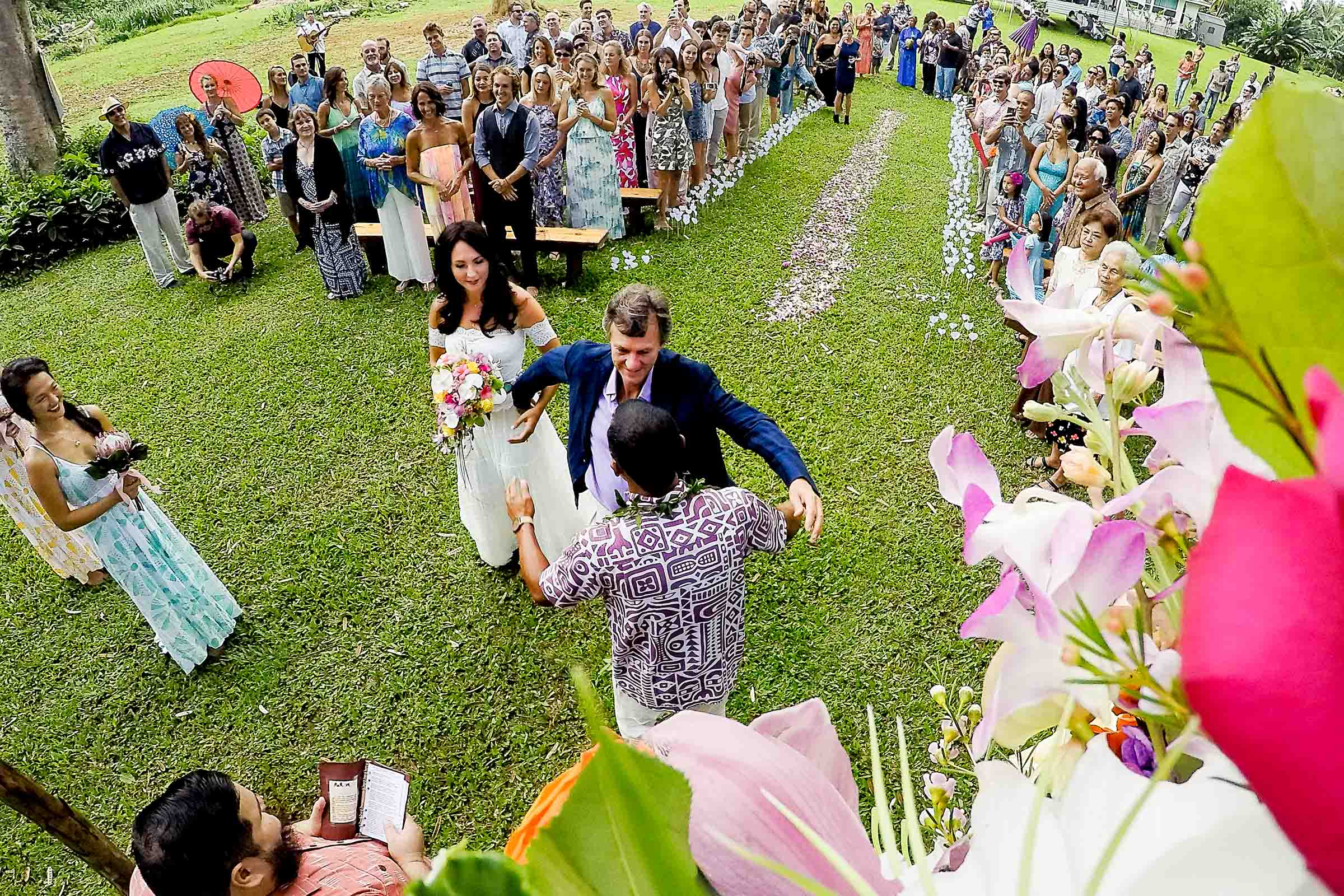 A father passing off his daughter to the groom and hugging him during a Kauai Island wedding ceremony amidst massive majestic acacias trees on a private estate