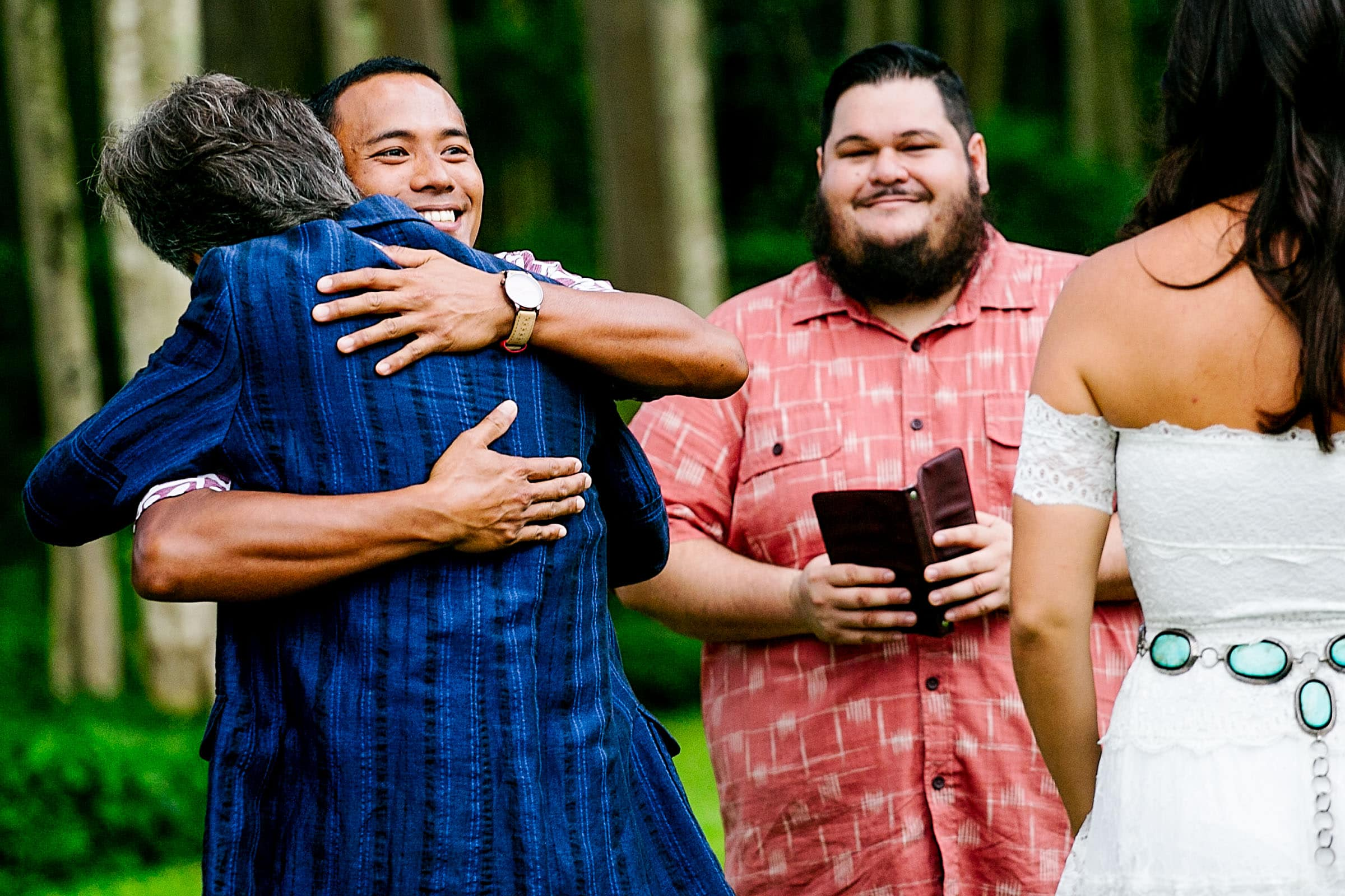 A groom hugging the father during a Kauai Island wedding ceremony amidst massive majestic acacias trees on a private estate