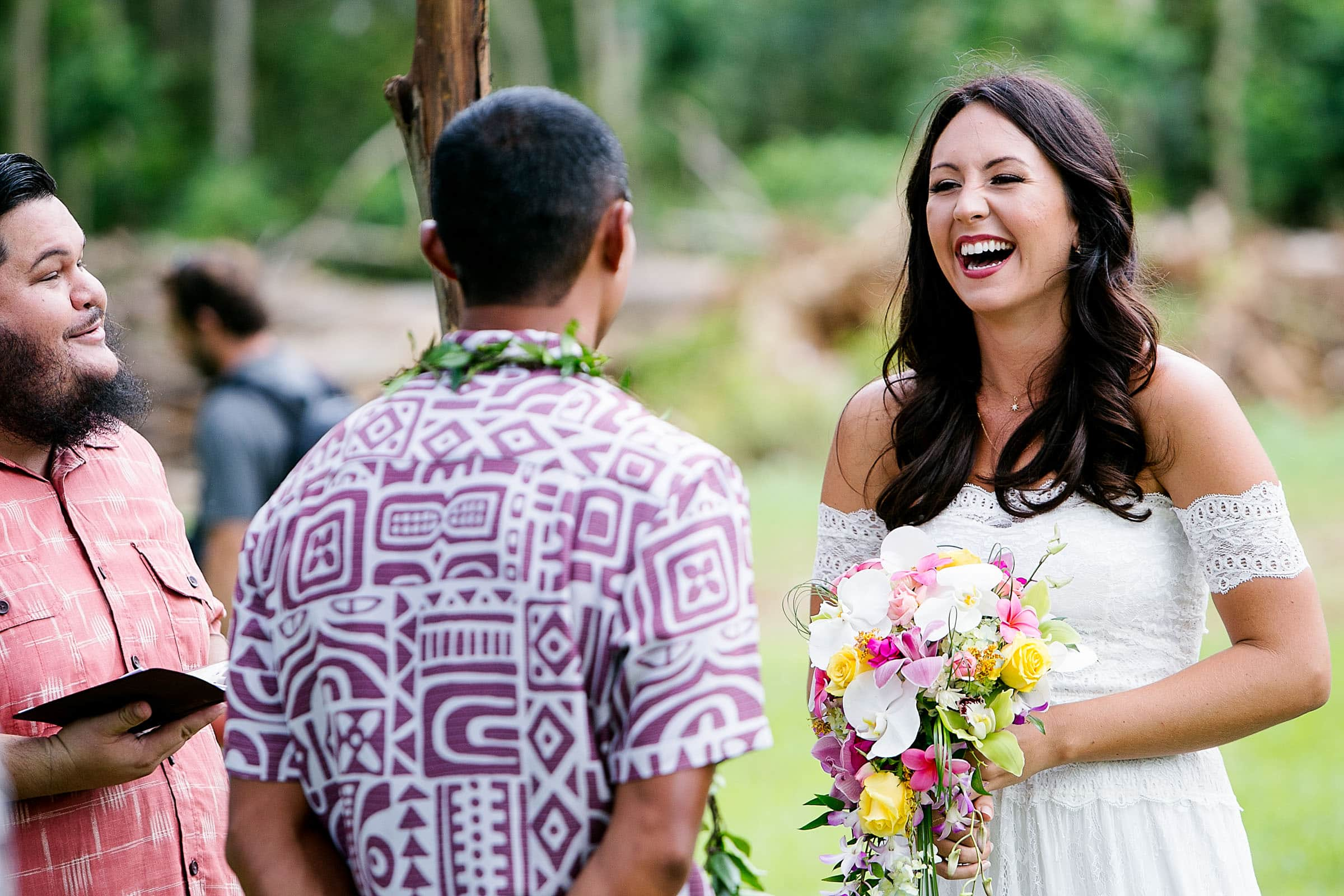 Beautiful bride laughing during her Kauai Island wedding ceremony amidst massive majestic acacias trees on a private estate