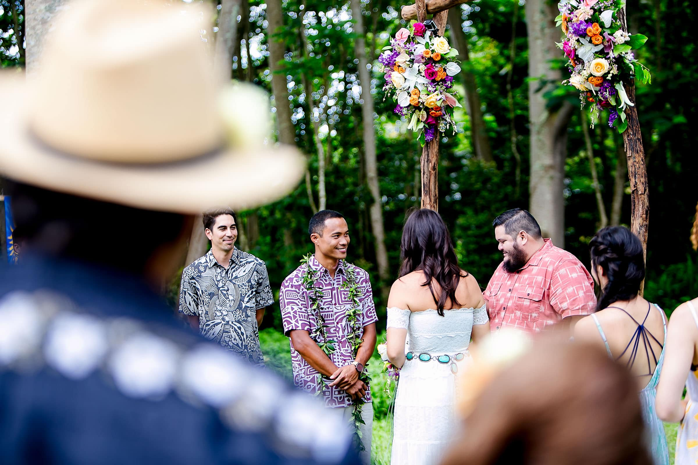 A view through guests on the bride and groom during a Kauai Island wedding ceremony amidst massive majestic acacias trees on a private estate