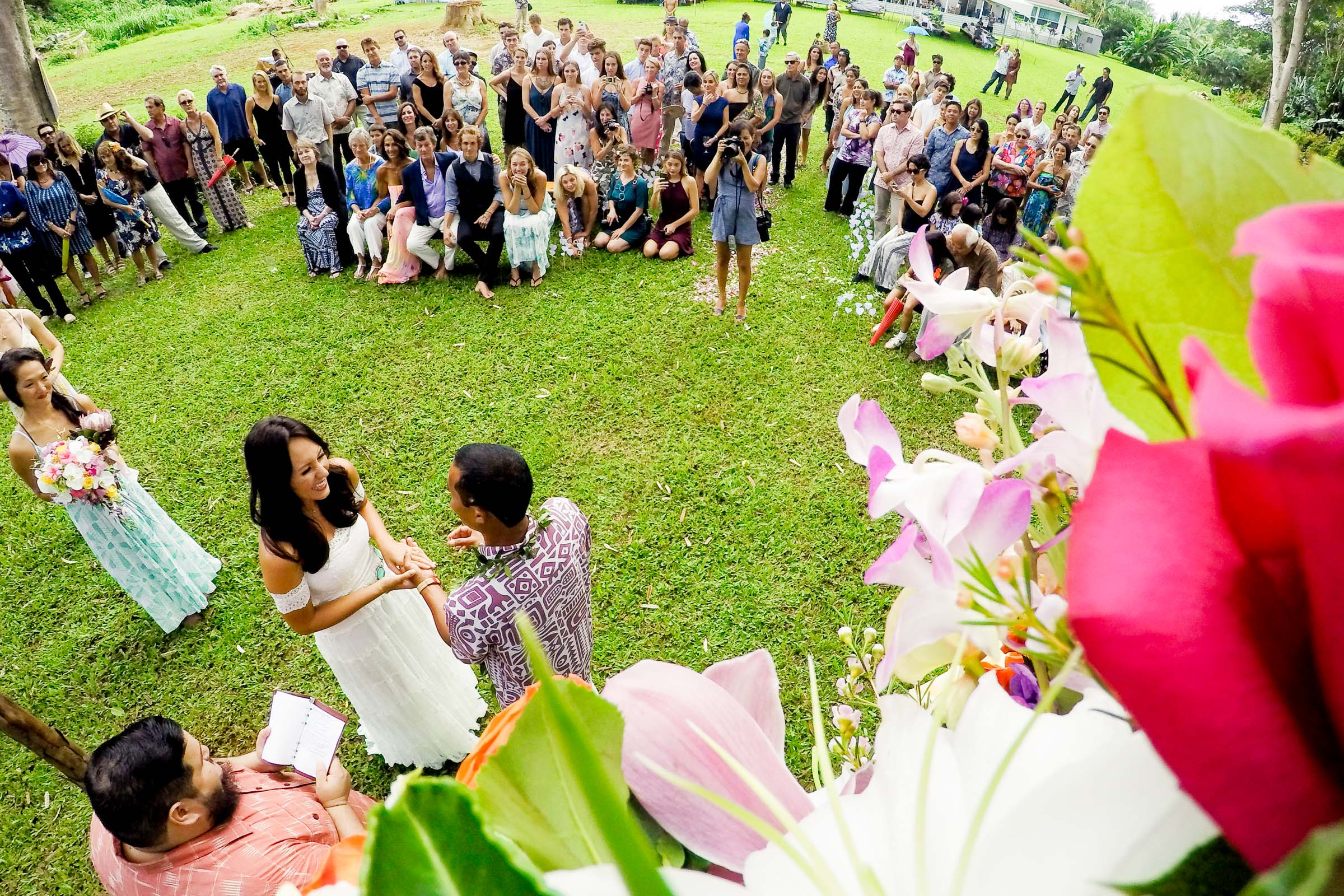 A wide angle perspective on the ceremony and guests during a Kauai Island wedding ceremony amidst massive majestic acacias trees on a private estate