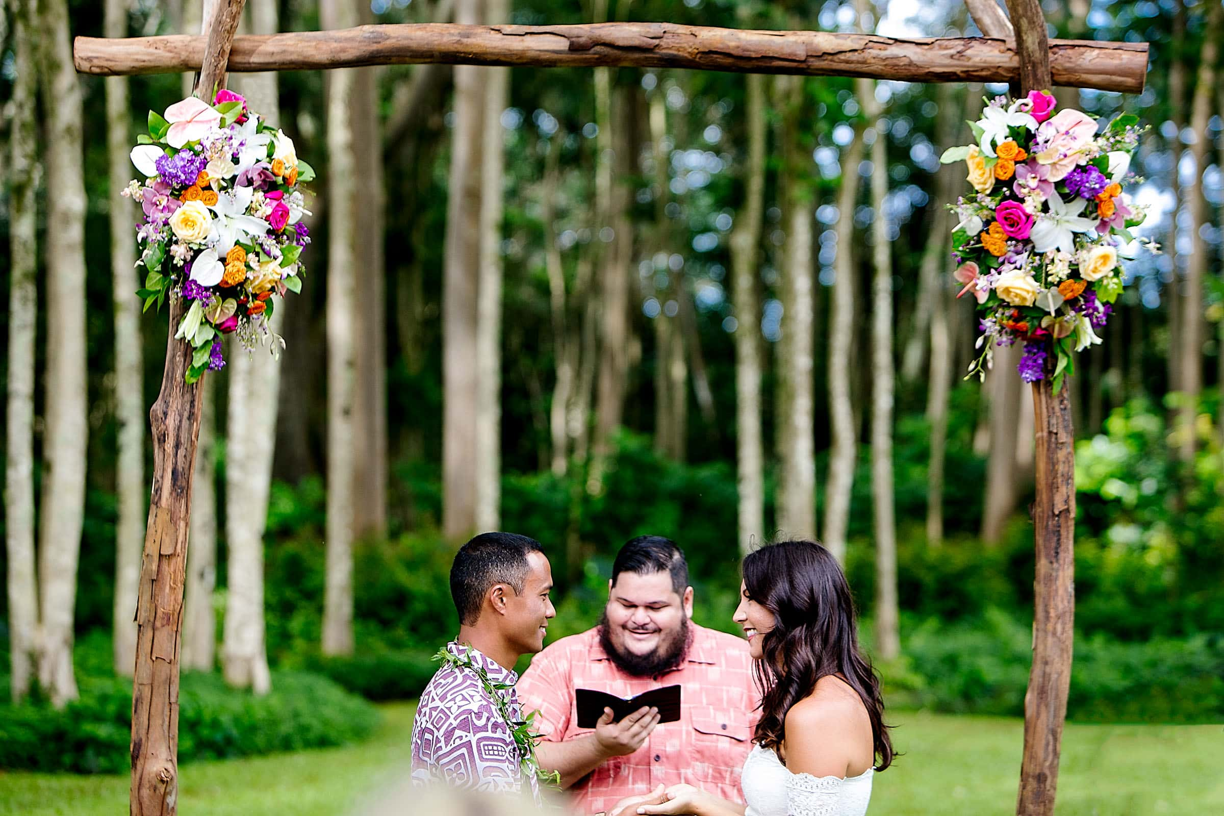 A bride and groom exchanging vows during their Kauai Island wedding ceremony amidst massive majestic acacias trees on a private estate