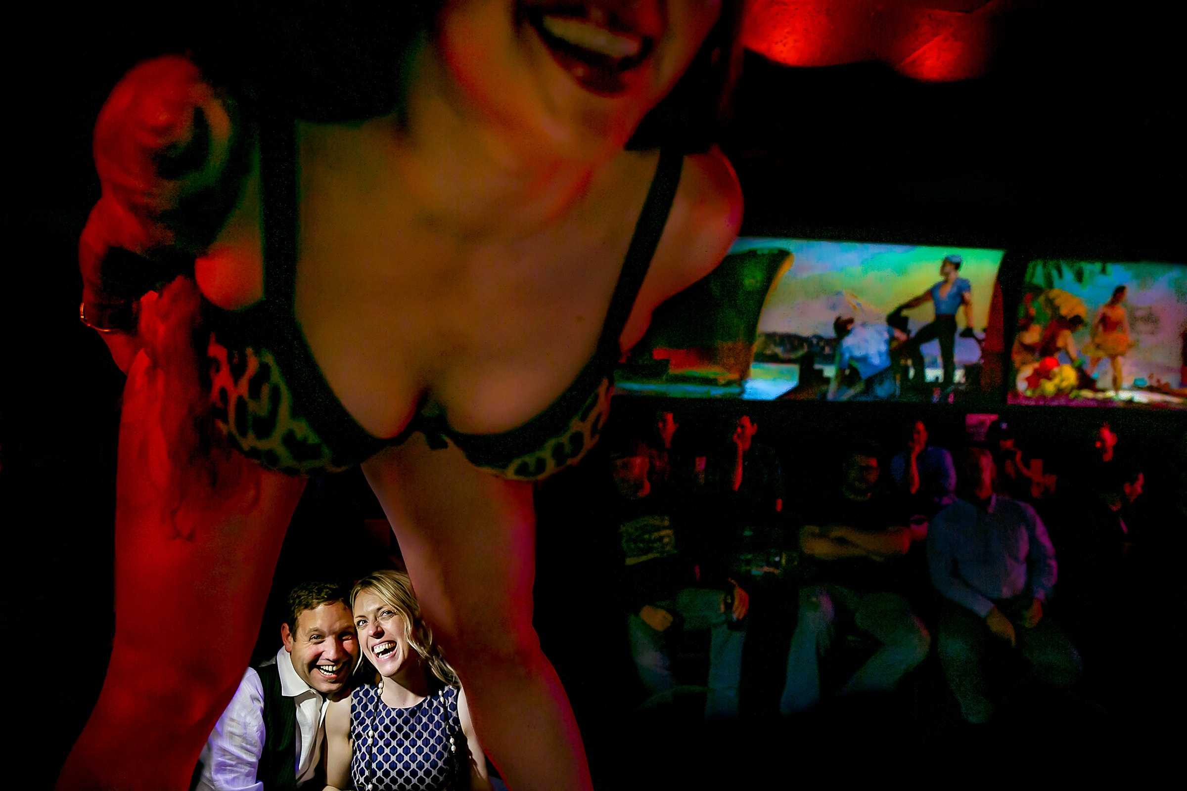 A fun night portrait of a couple enjoying entertainment during their Portland Engagement Date photo shoot at Mary's Club