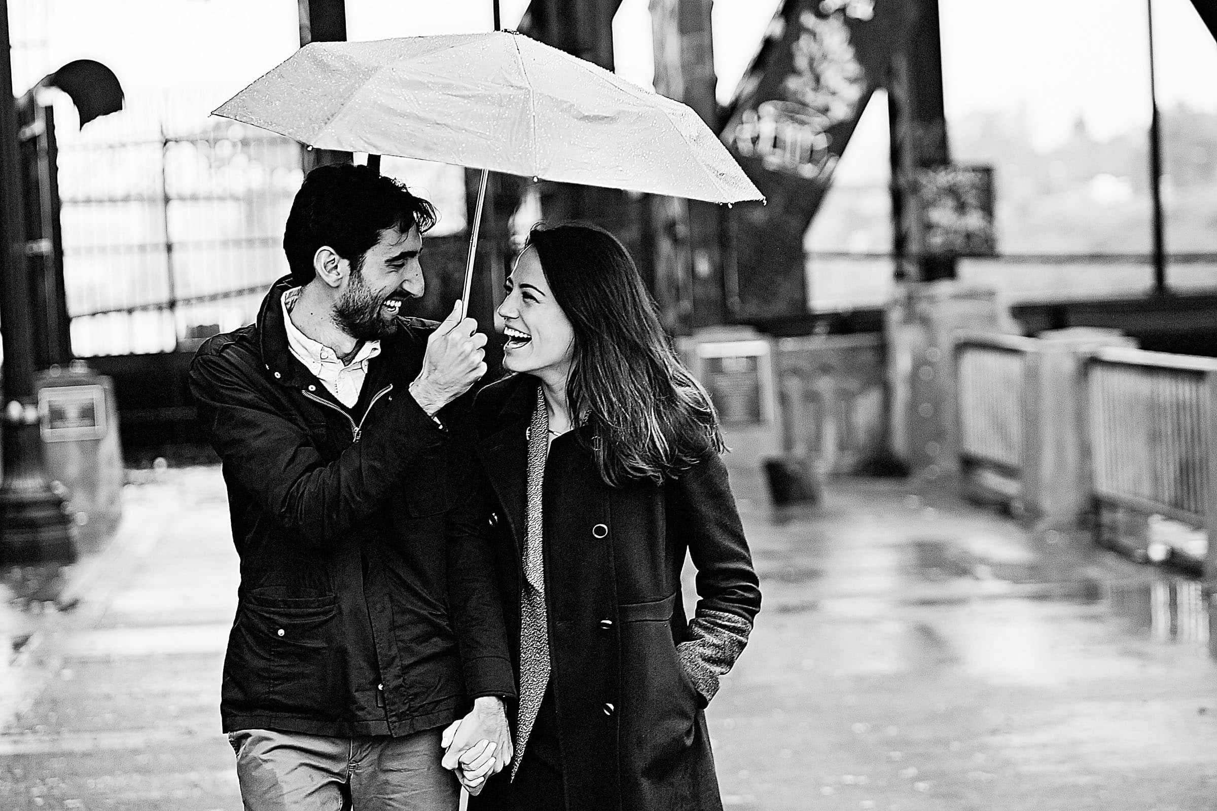 A fun walking Portland engagement proposal photo under an umbrella along the Portland waterfront park