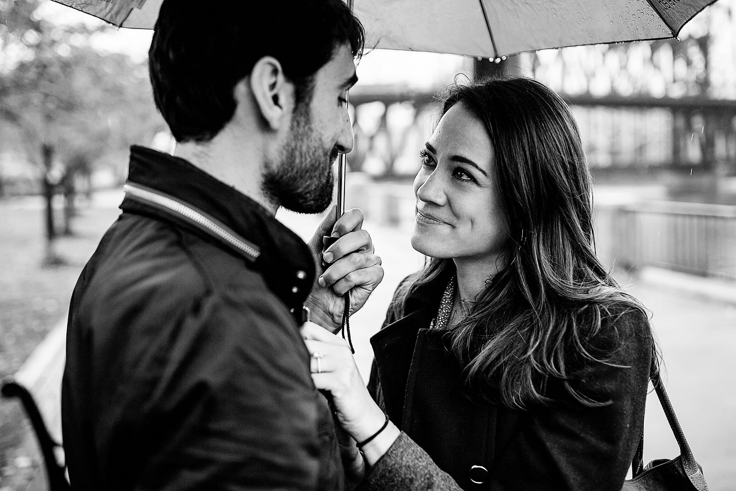 An emotional Portland engagement proposal photo under an umbrella on the waterfront park