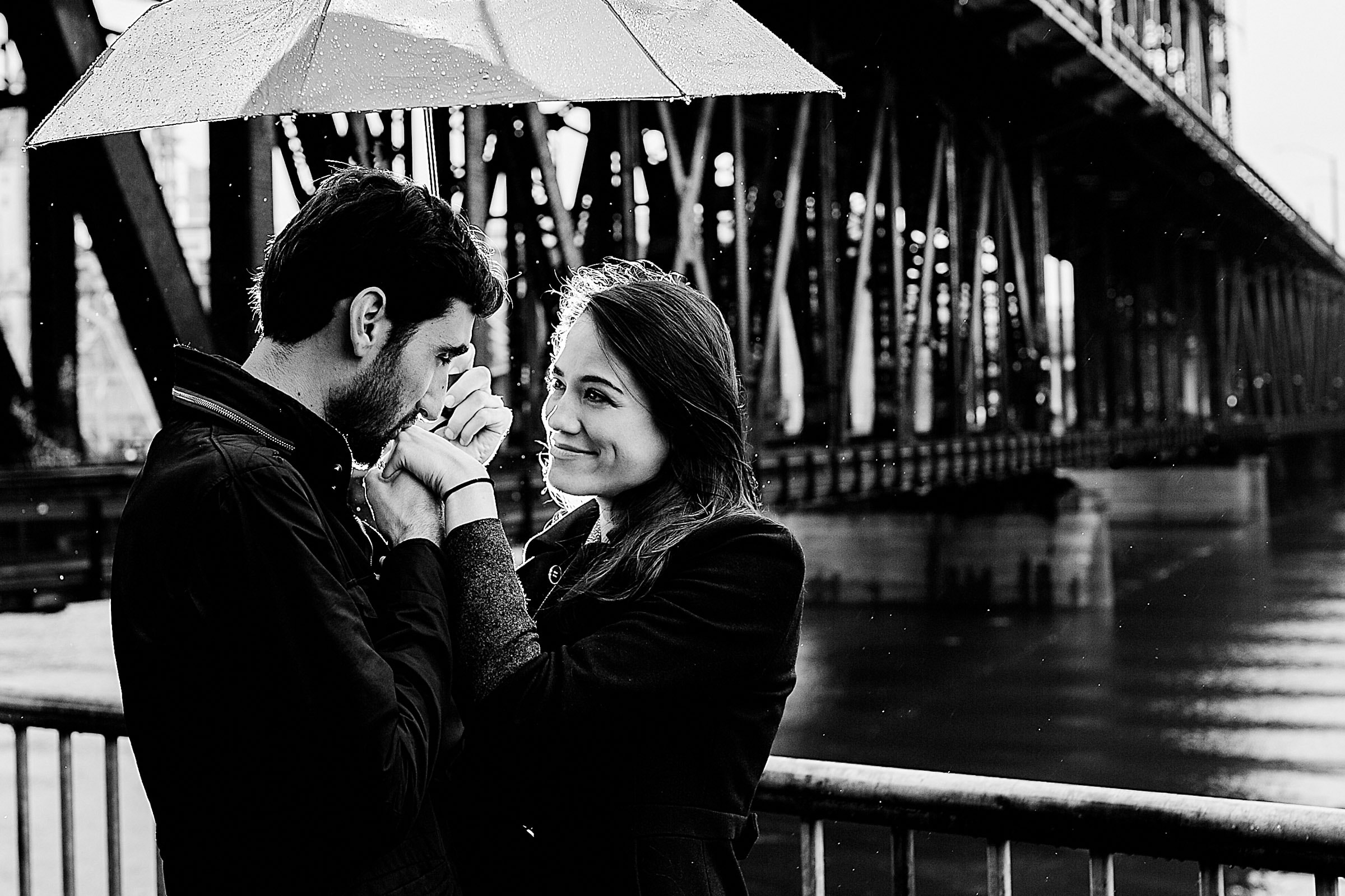 An emotional Portland engagement proposal photo under an umbrella along the Portland waterfront park with beautiful light