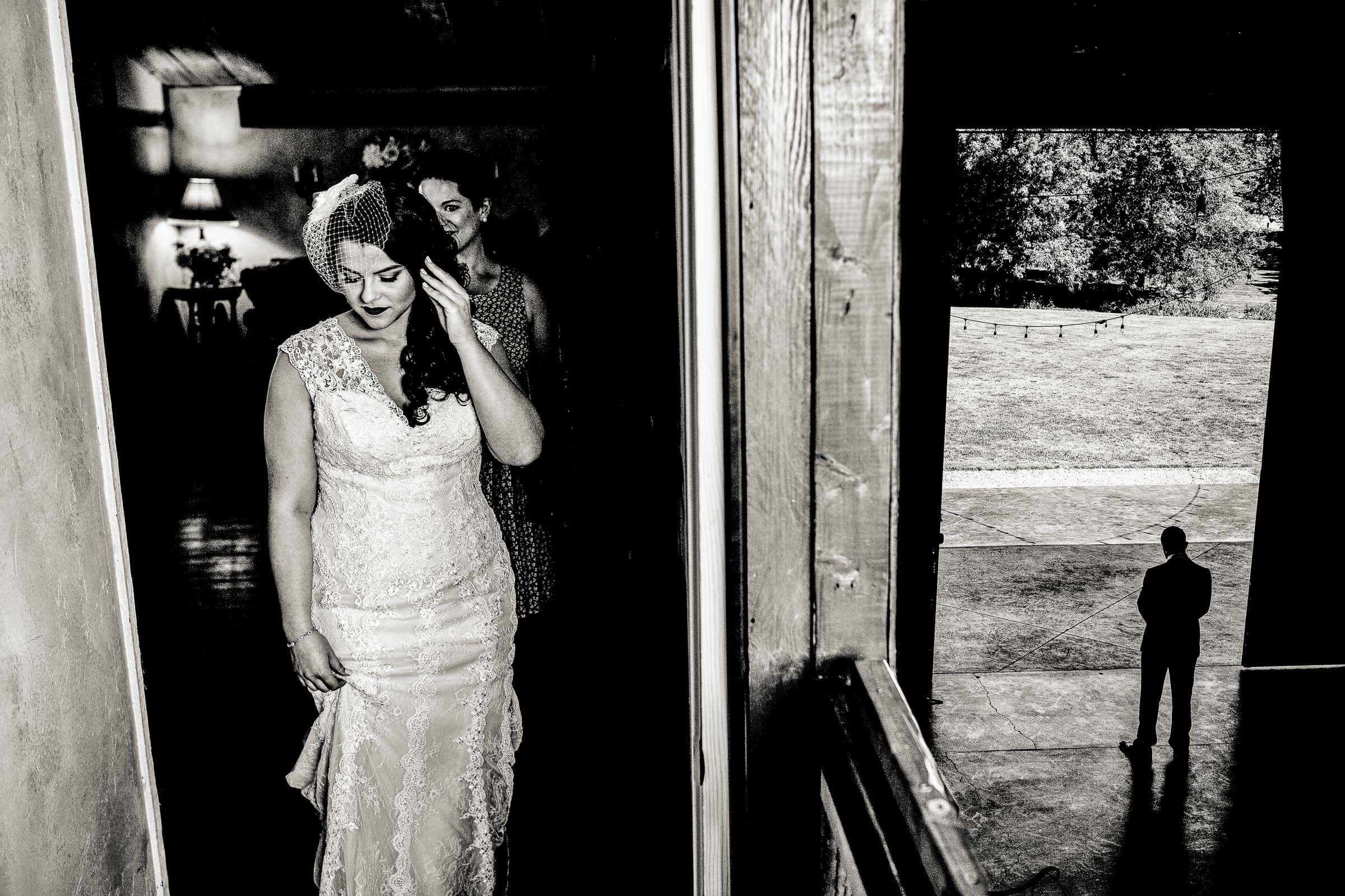 An story telling photo of a bride walking out to see her groom moments before their Postlewait's Country wedding located in the heart of the Willamette Valley between Portland and Salem near Aurora, Oregon