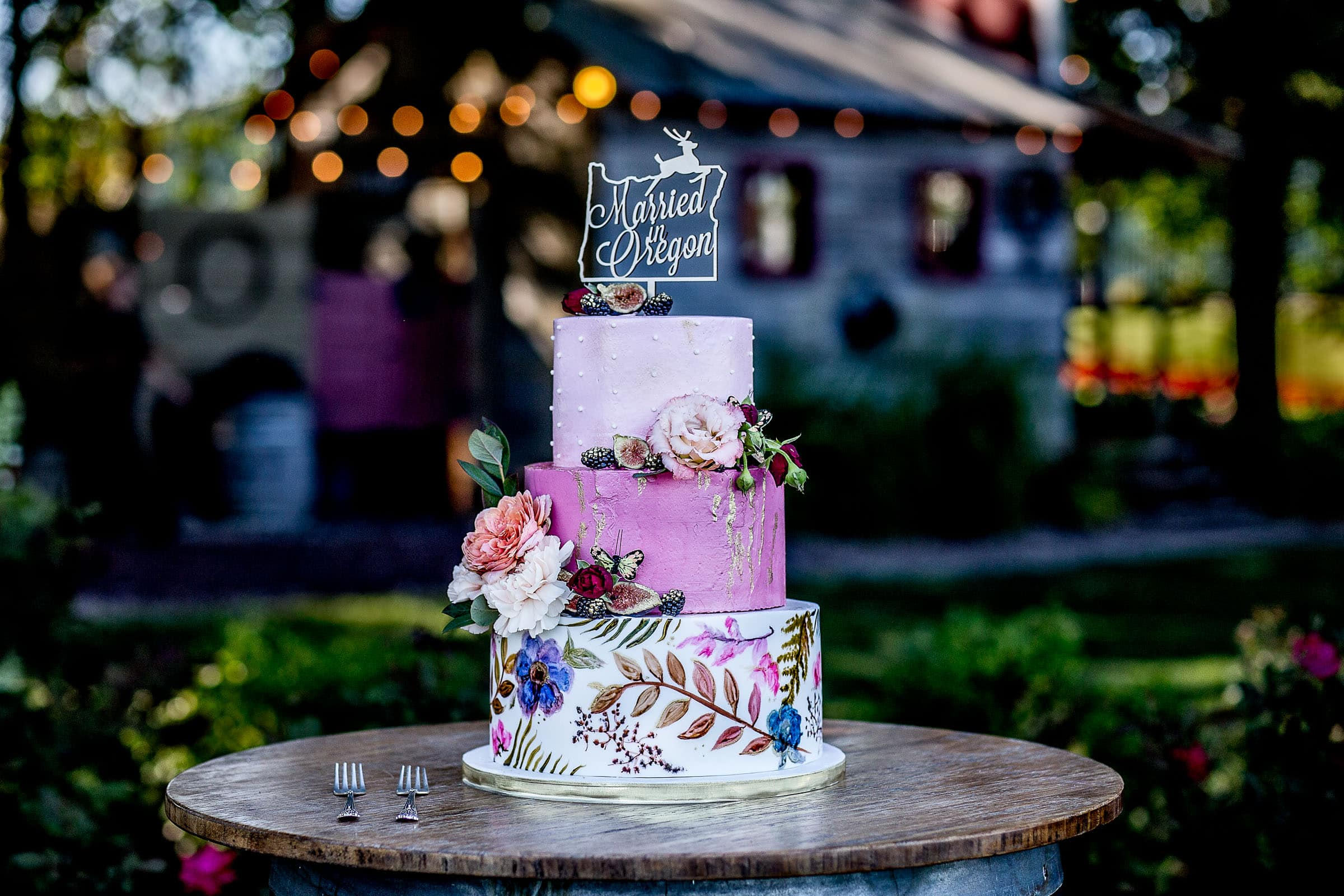 A stunning colorful cake made by Lux Sucre during a Postlewait's Country wedding located in the heart of the Willamette Valley between Portland and Salem near Aurora, Oregon