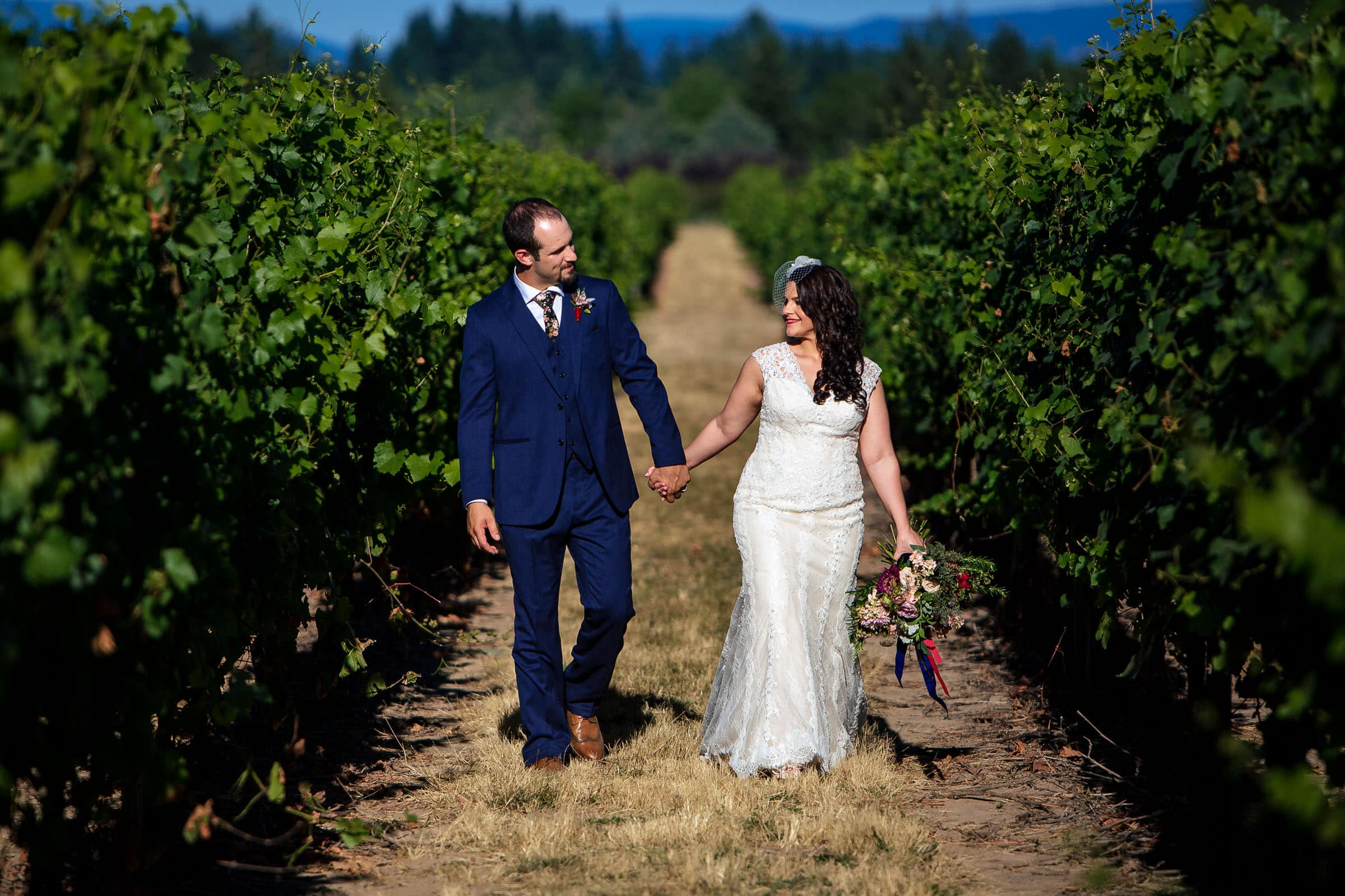 A beautiful bride and groom walking together in a vineyard during their Postlewait's Country wedding located in the heart of the Willamette Valley between Portland and Salem near Aurora, Oregon