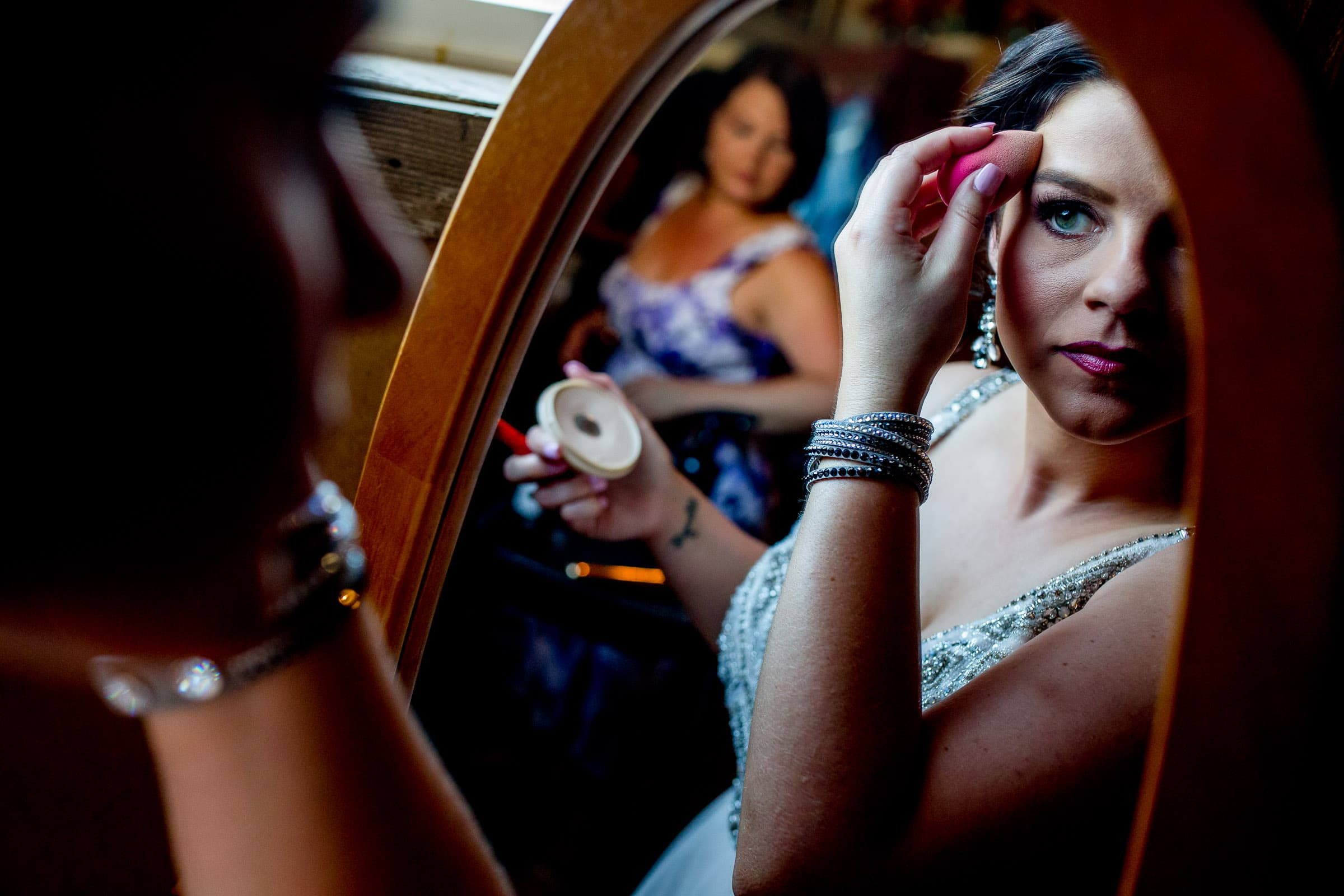 A stunning and elegant bride putting on her makeup during her Postlewait's Country wedding located in the heart of the Willamette Valley between Portland and Salem near Aurora, Oregon