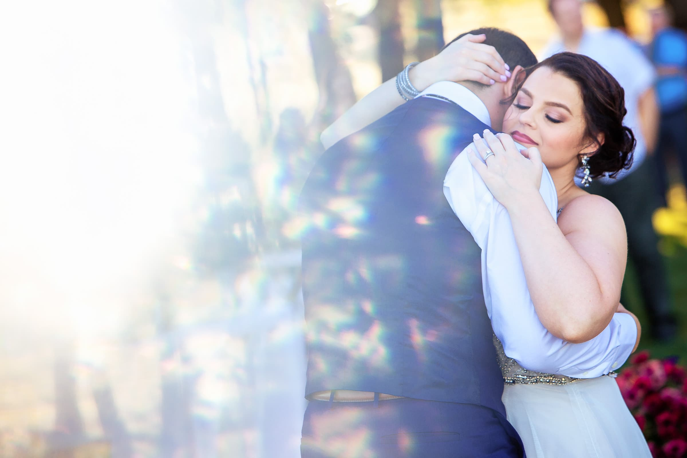 A beautiful bride embracing her groom during their first dance at their Postlewait's Country wedding located in the heart of the Willamette Valley between Portland and Salem near Aurora, Oregon