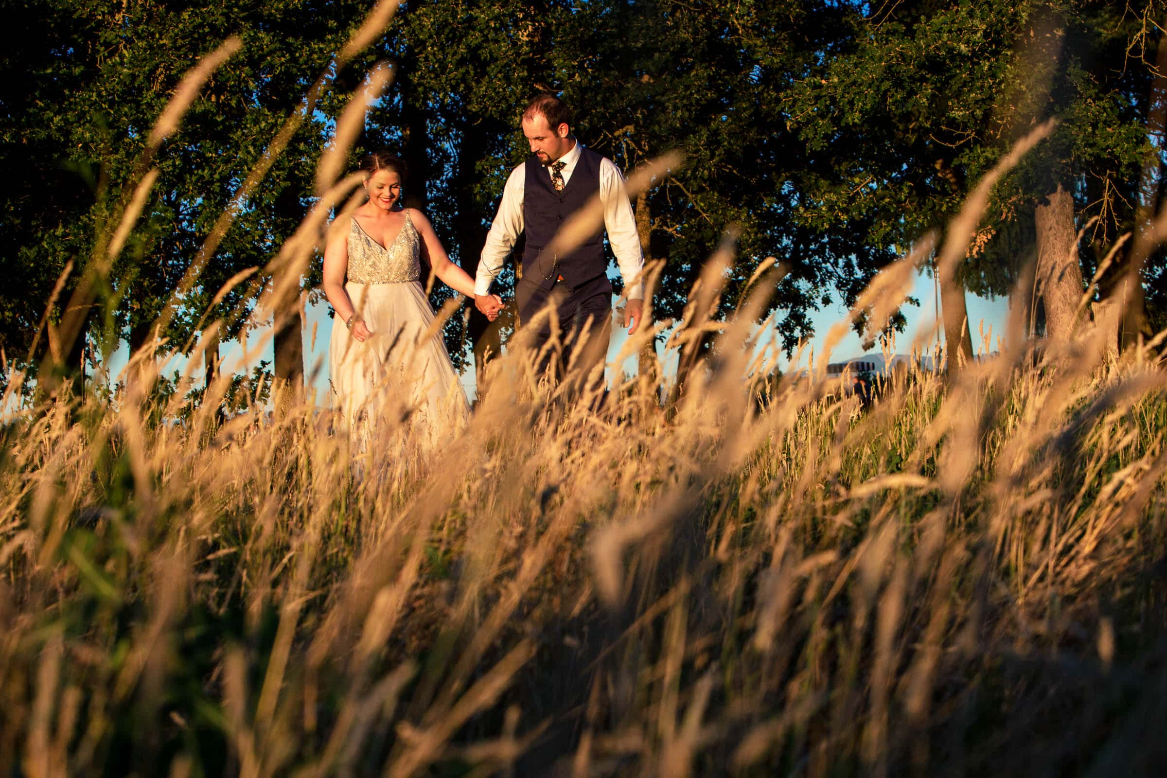 An intimate photo taken through a wheat field during a Postlewait's Country wedding located in the heart of the Willamette Valley between Portland and Salem near Aurora, Oregon