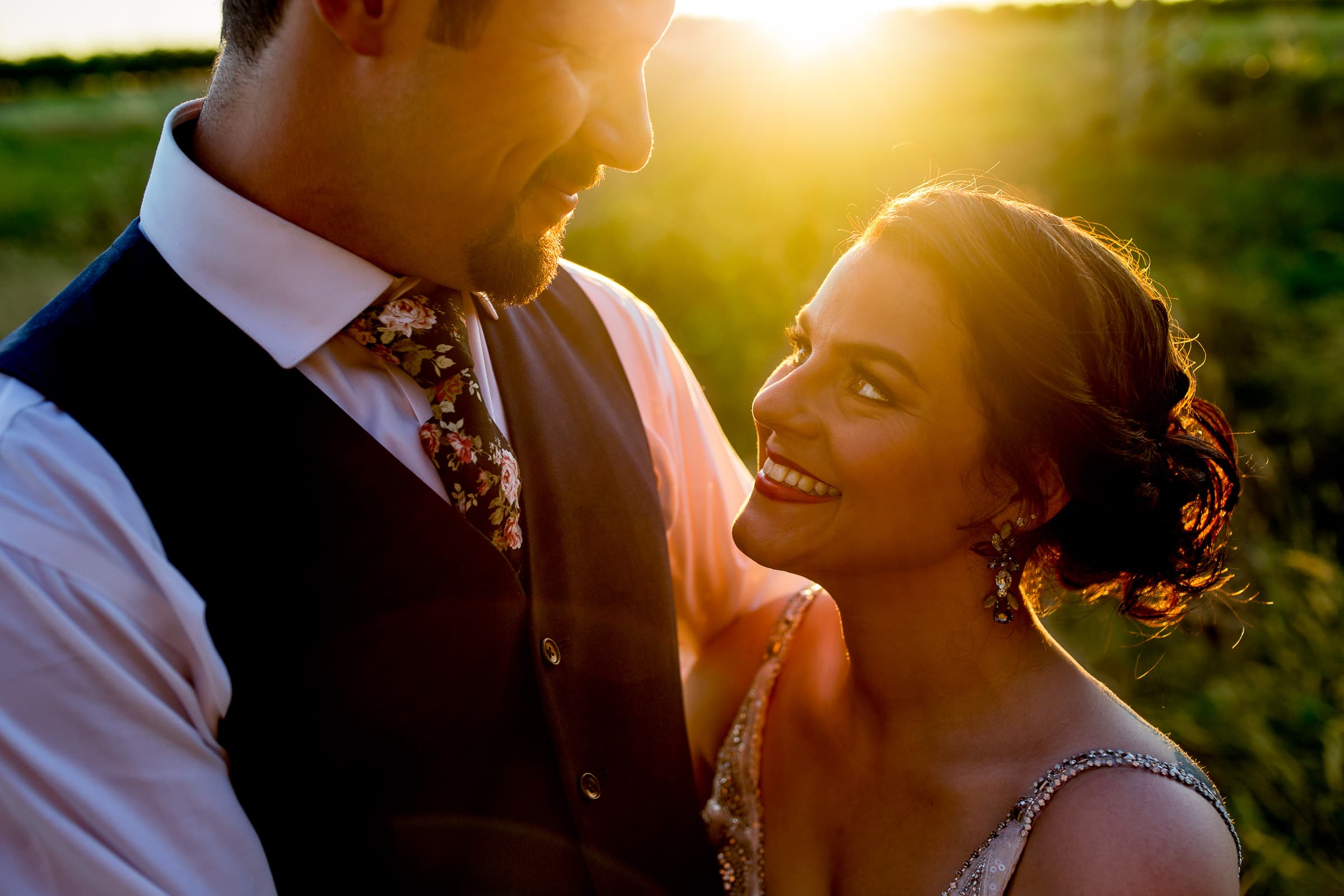 Gorgeous warm back light on a bride and groom holding each other during their Postlewait's Country wedding located in the heart of the Willamette Valley between Portland and Salem near Aurora, Oregon