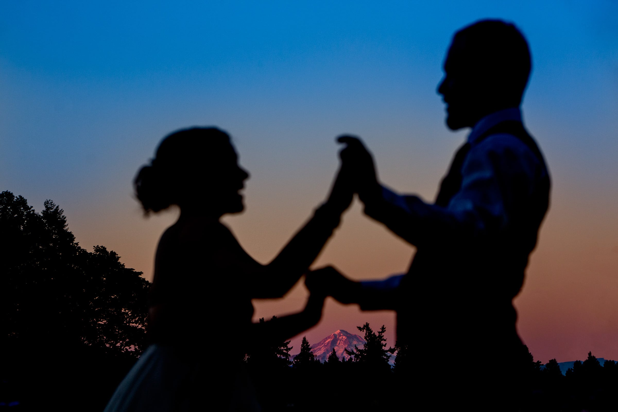 A creative silhouette of a bride and groom dancing with Mt Hood in the distance during their Postlewait's Country wedding located in the heart of the Willamette Valley between Portland and Salem near Aurora, Oregon