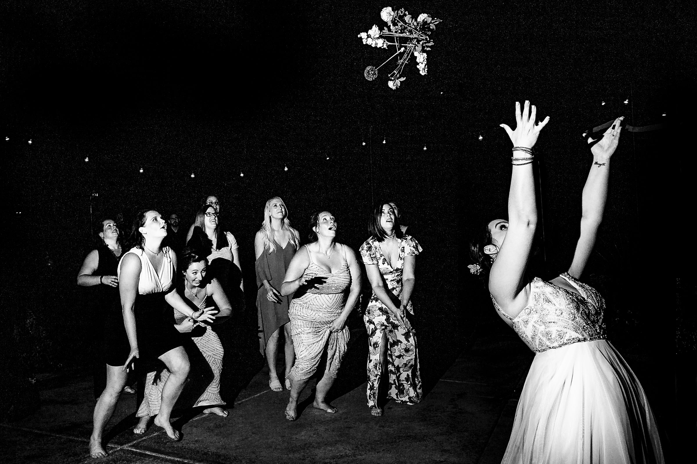 A fun photo of a bride throwing her bouquet during a Postlewait's Country wedding located in the heart of the Willamette Valley between Portland and Salem near Aurora, Oregon