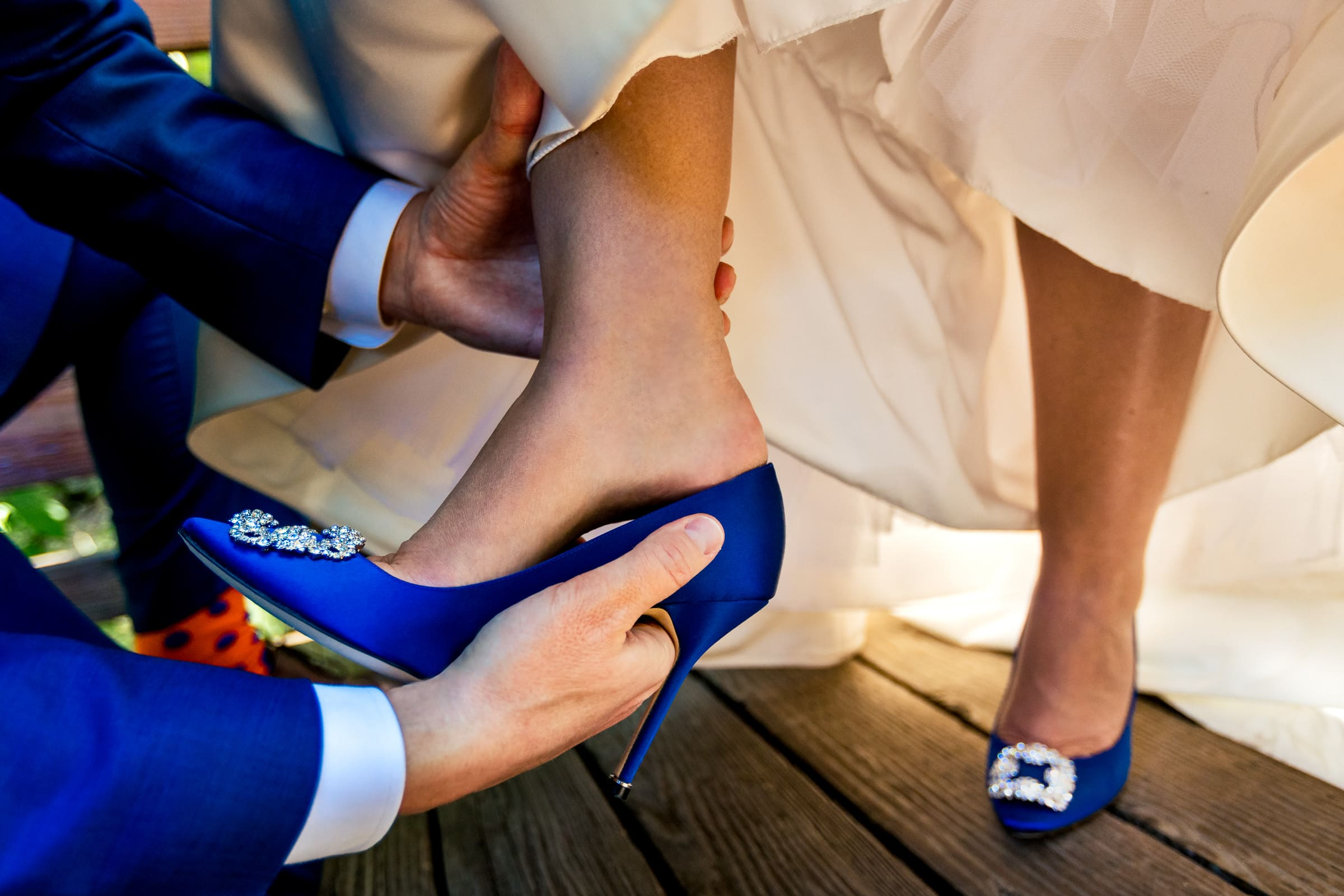Groom putting shoes on bride getting ready for their Abernethy Center Portland Wedding in Oregon City
