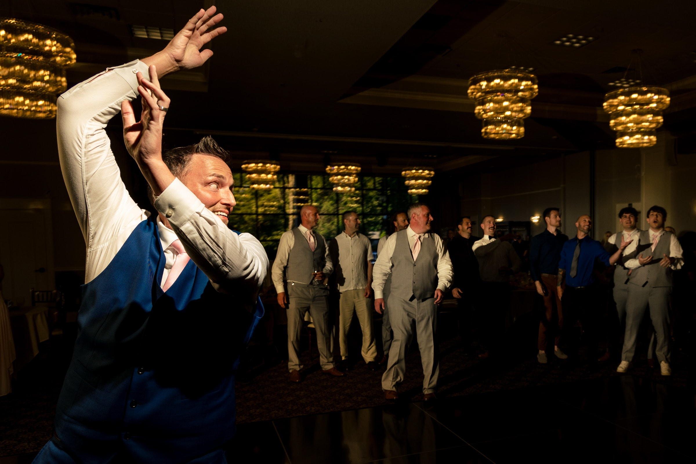Groom tossing to the groomsmen during an Abernethy Center Portland Wedding reception in Oregon City