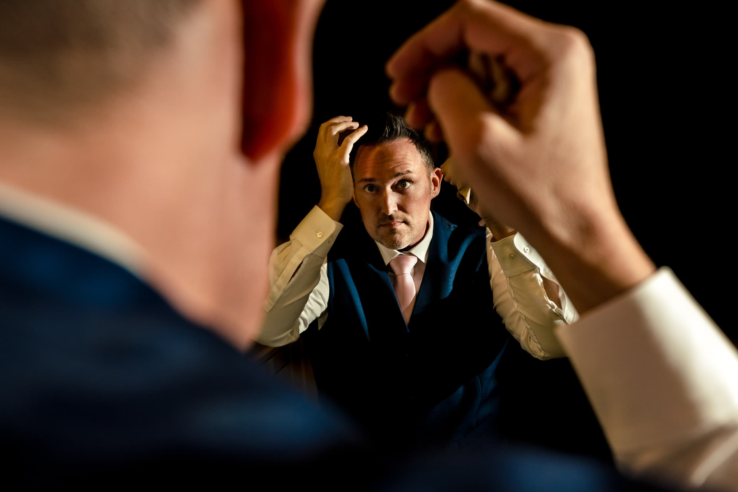 Groom fixing his hair while getting ready for his Abernethy Center Portland Wedding in Oregon City