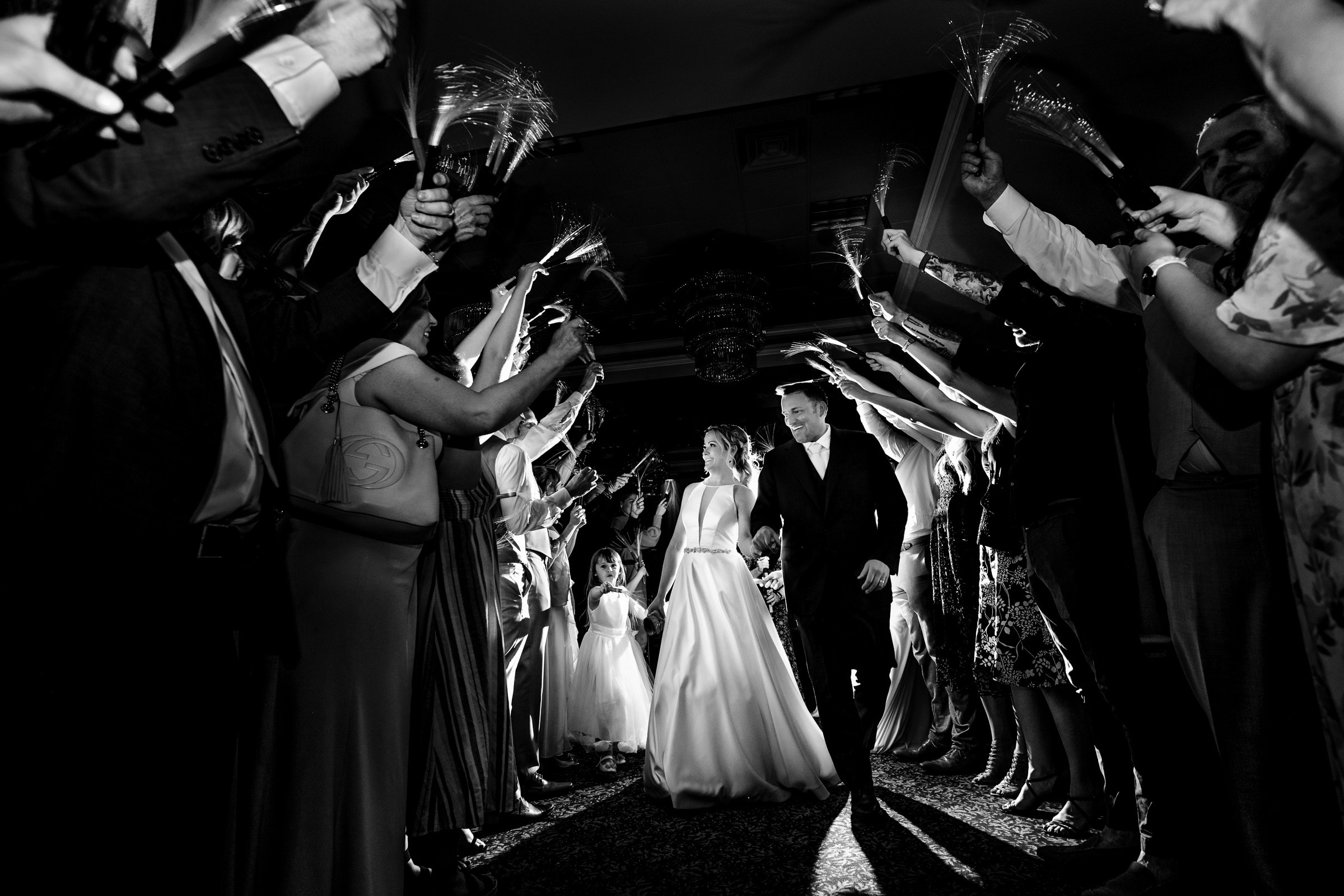 Bride and groom exiting through family and friends holding glow in the dark batons during their Abernethy Center Portland Wedding reception in Oregon City