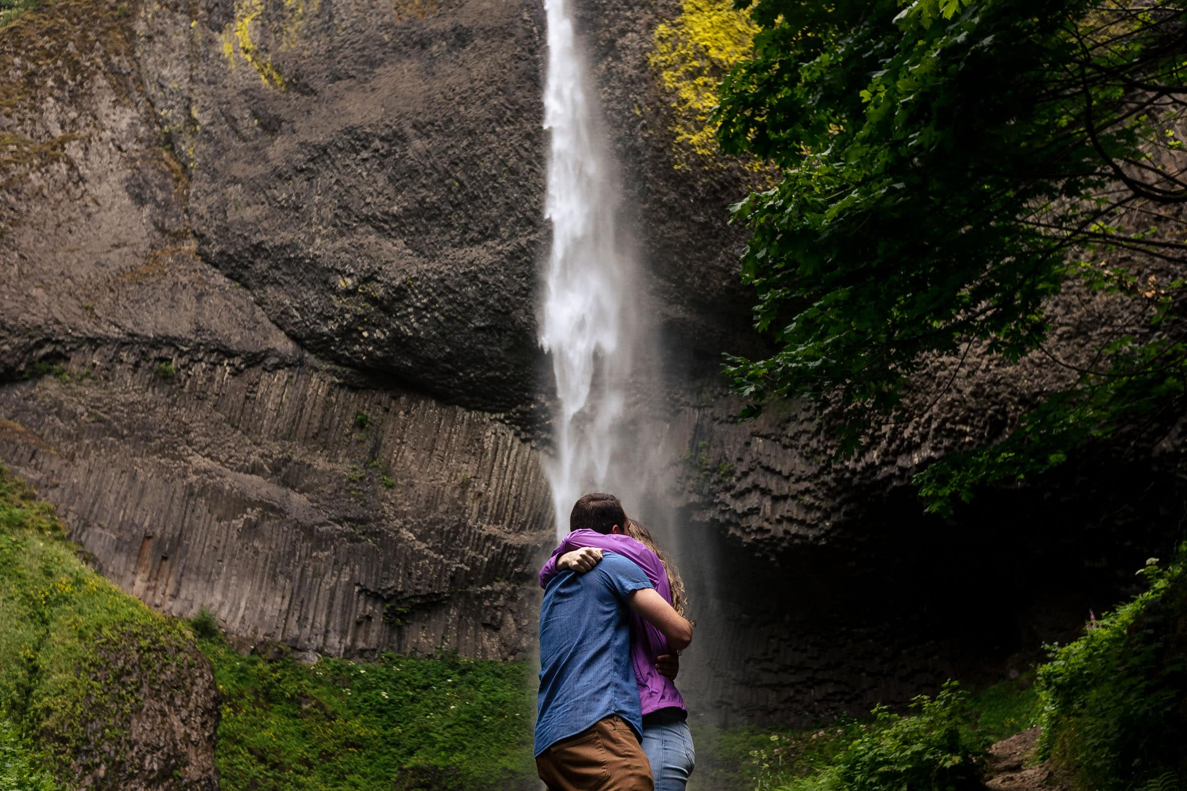 A couple embracing in a big hug under Latourell Waterfalls just after he proposed to her. Photo by josandtree.