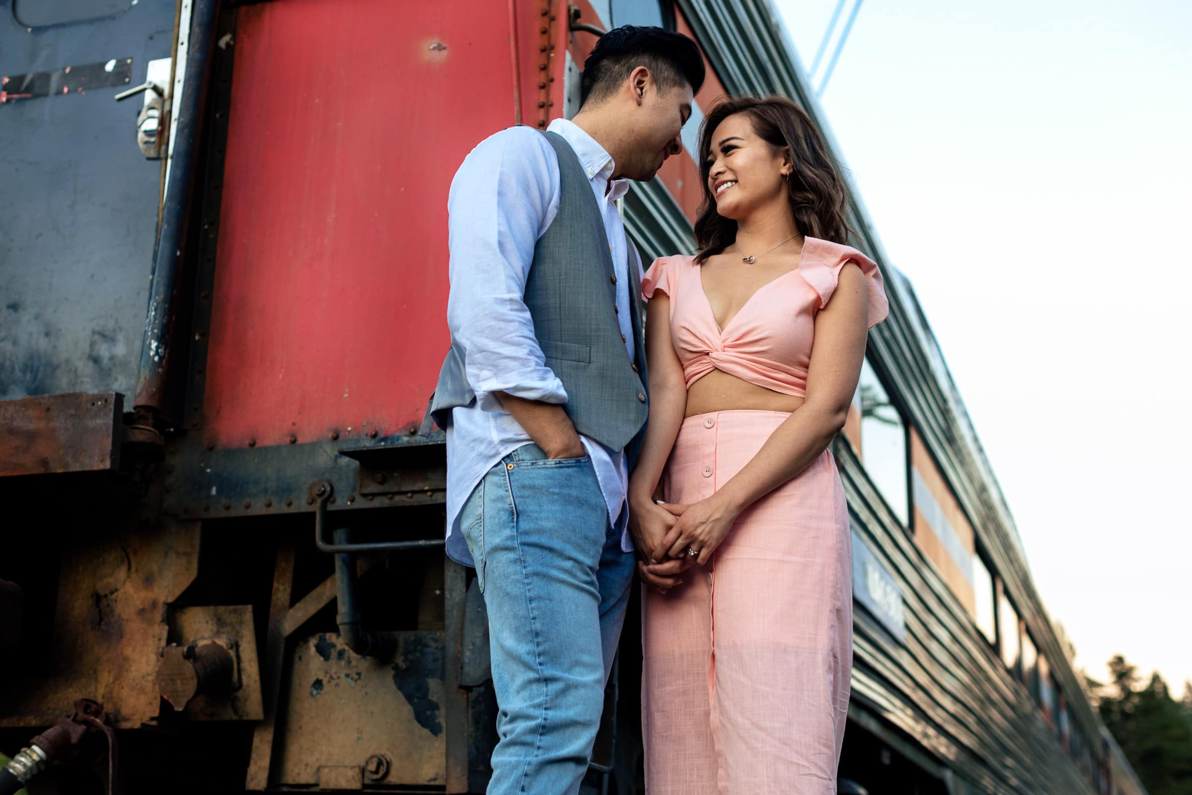 Super cute couple holding each other near a train for their Lavender Valley Engagement Photos