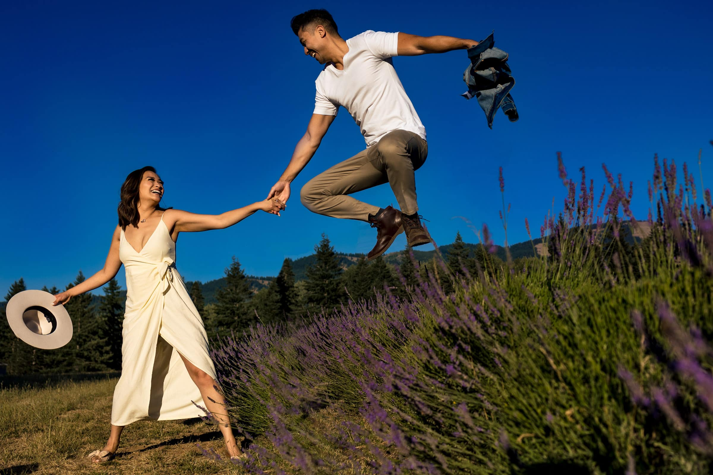 A couple jumping over lavender during their Lavender Valley Engagement Photos