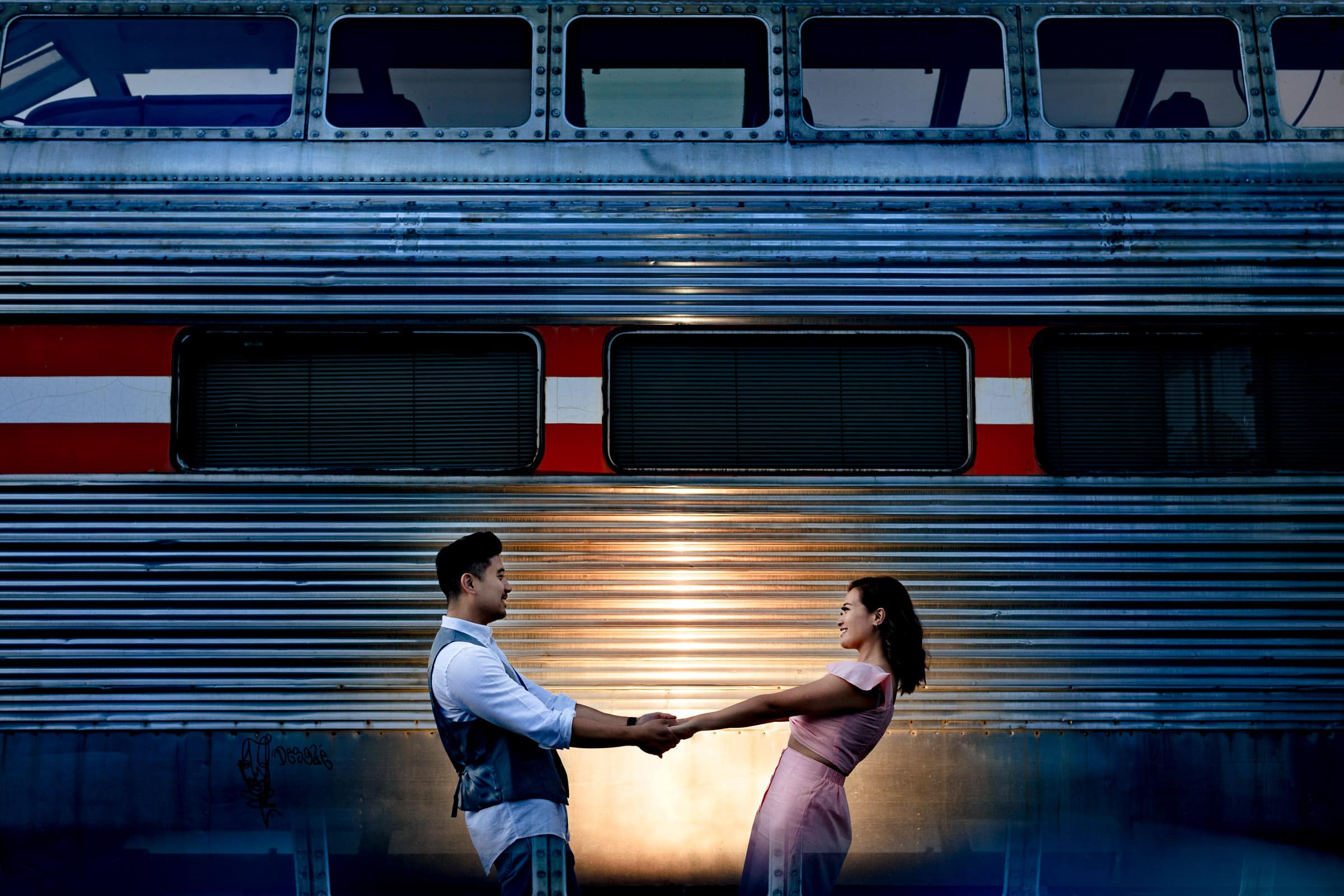 Fun couple lit up near a train for their Lavender Valley Engagement Photos