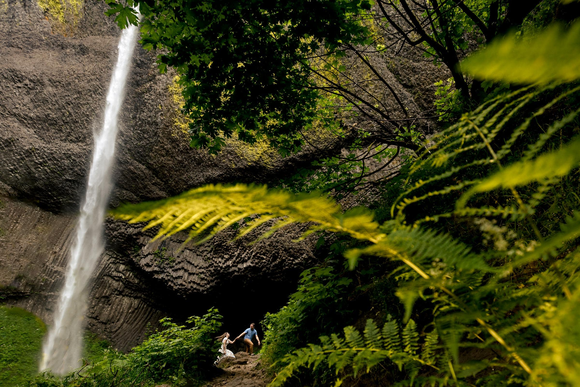 Couple walking through Latourell waterfalls after their proposal moment. Best Engagement Photography Locations in Portland. Latourell Falls Engagement Photos by Jos and Tree, portland wedding photographers.