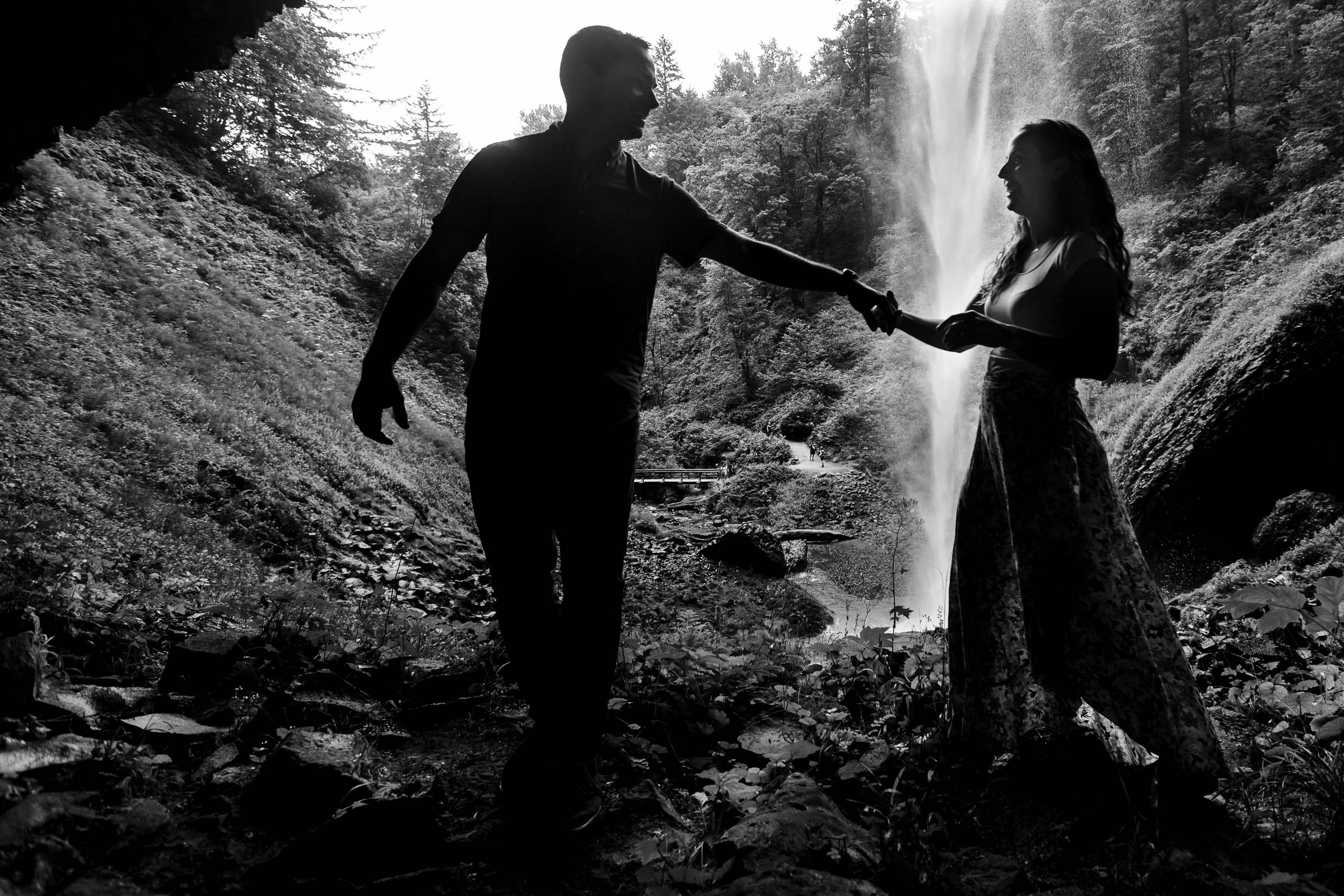 Engagement photos of a couple walking under Latourell Falls cave shortly after their real proposal moment. Best Engagement Photography Locations in Portland. Latourell Falls Engagement Photos by Jos and Tree, portland wedding photographers.