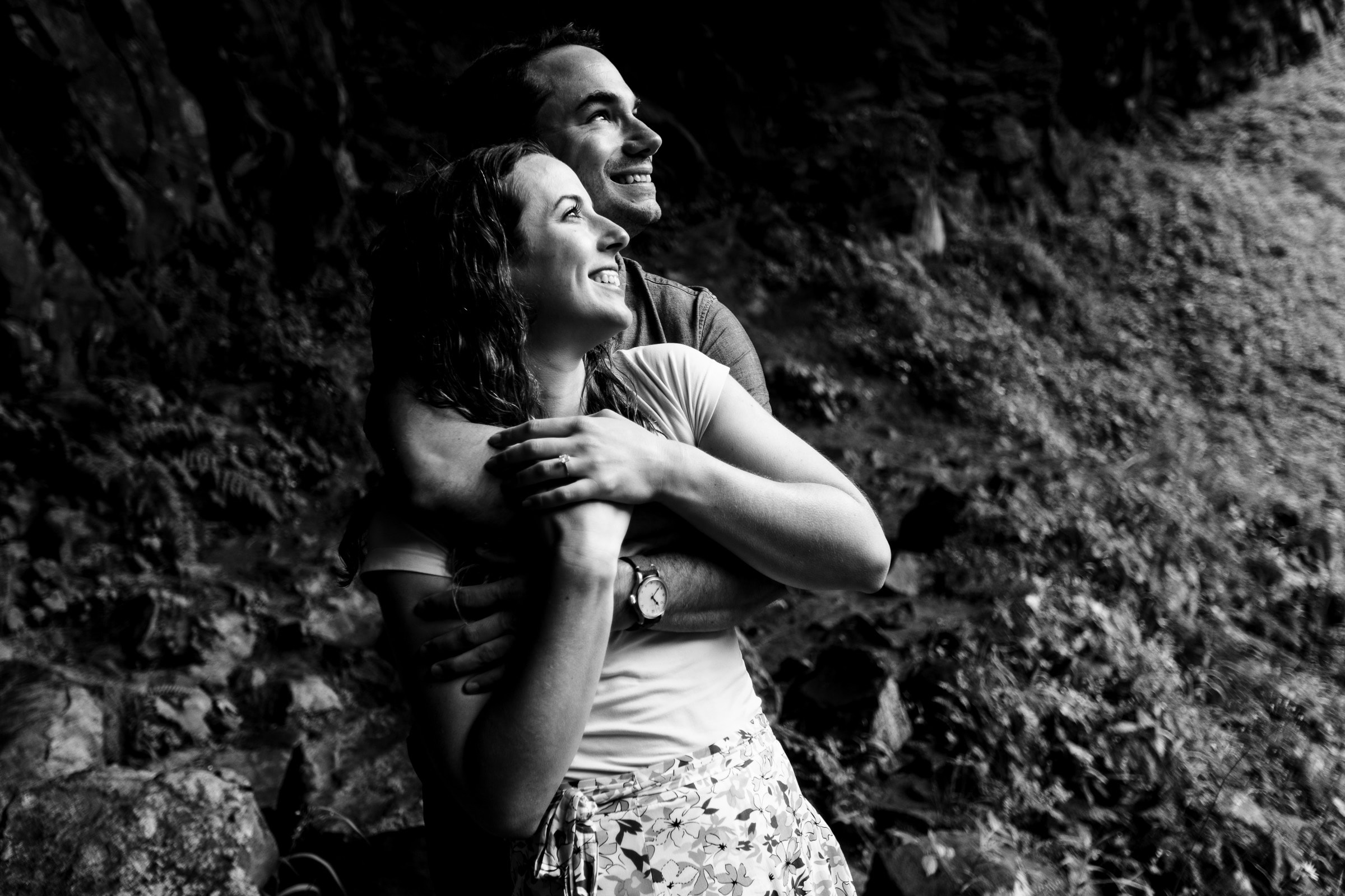 Beautiful black and white portrait of a couple holding each other while looking up at Latourell Falls moments after their real proposal moment. Best Engagement Photography Locations in Portland. Latourell Falls Engagement Photos by Jos and Tree, portland wedding photographers.