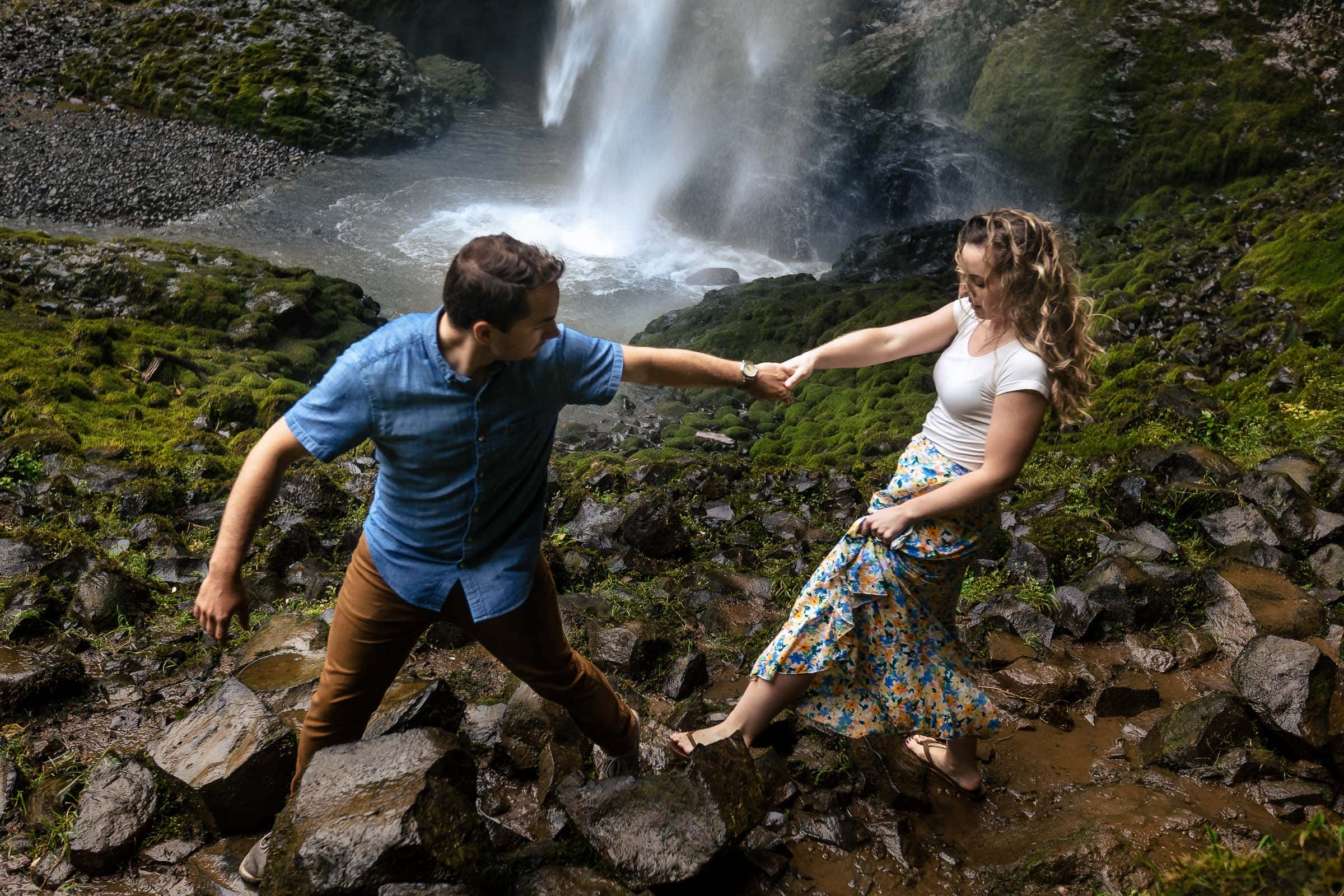 A couple walking hand and hand on rocks under Latourell Falls moments after their real proposal moment. Best Engagement Photography Locations in Portland. Latourell Falls Engagement Photos by Jos and Tree, portland wedding photographers.