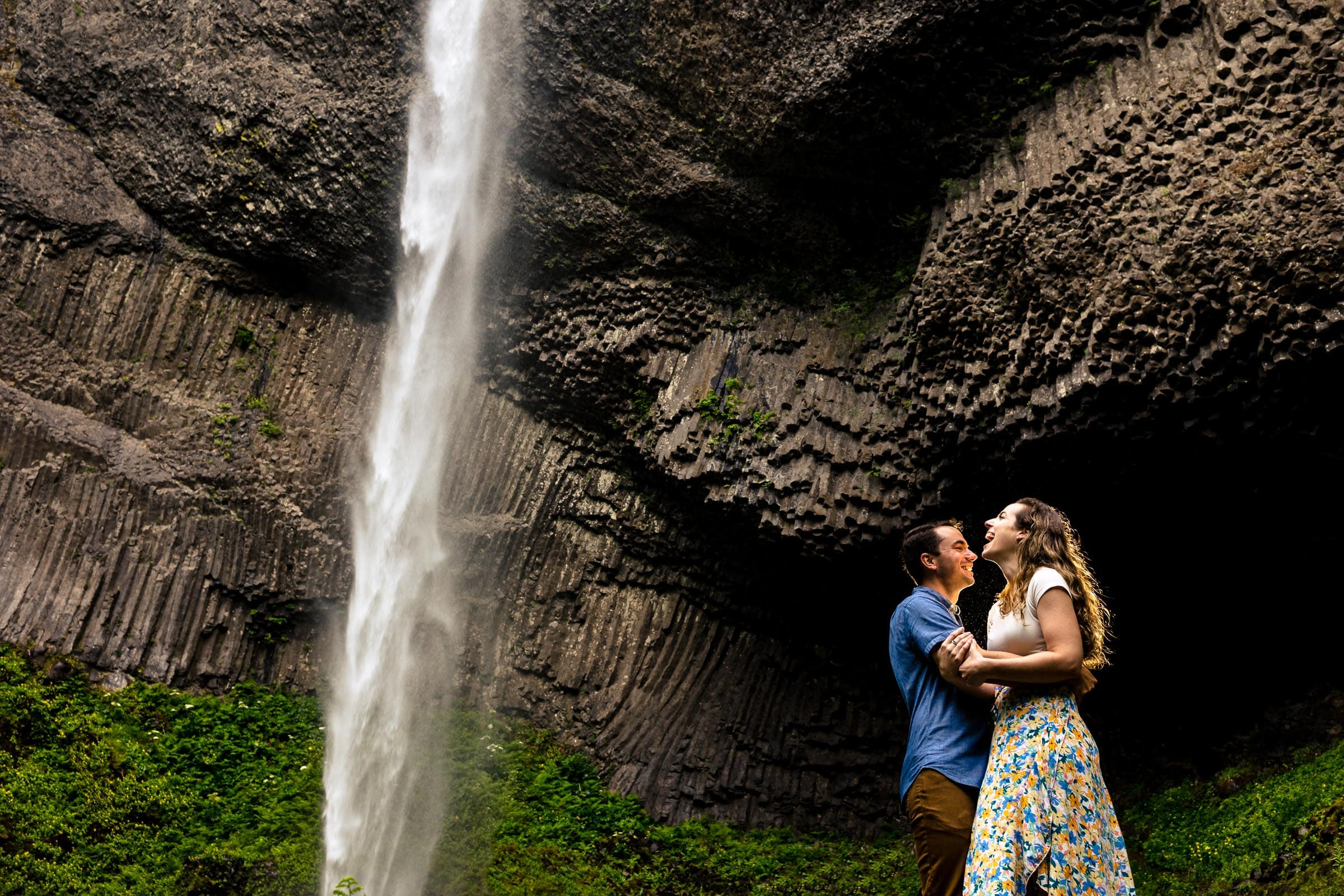 A couple laughing and holding each other under Latourell Falls just after their real proposal engagementmoment. Best engagement photos at Latourell Falls outside Portland near Multnomah Falls. Latourell Falls Engagement Photos by Jos and Tree.