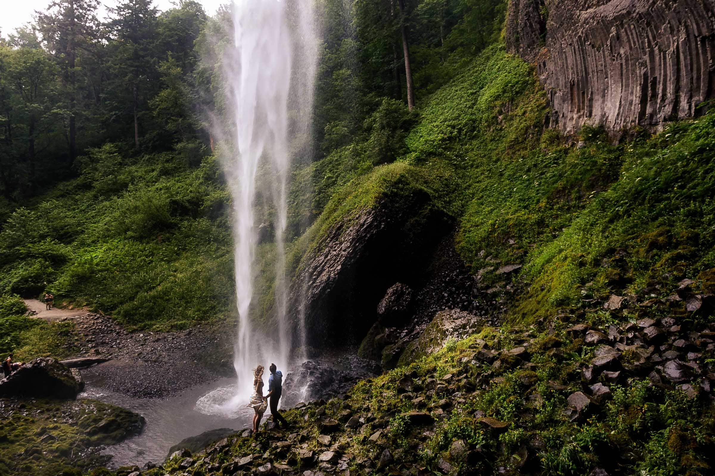 Couple looking up at Latourell waterfalls after their proposal moment. Best Engagement Photography Locations in Portland. Latourell Falls Engagement Photos by Jos and Tree, portland wedding photographers.