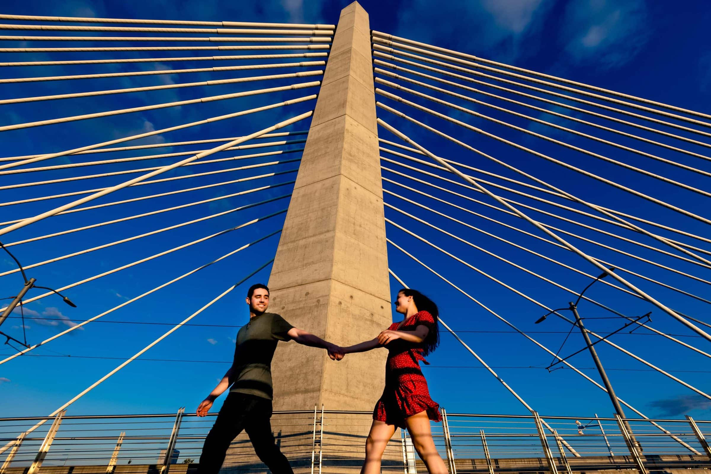 A fun moment with a couple running for their Tilikum Bridge engagement photos