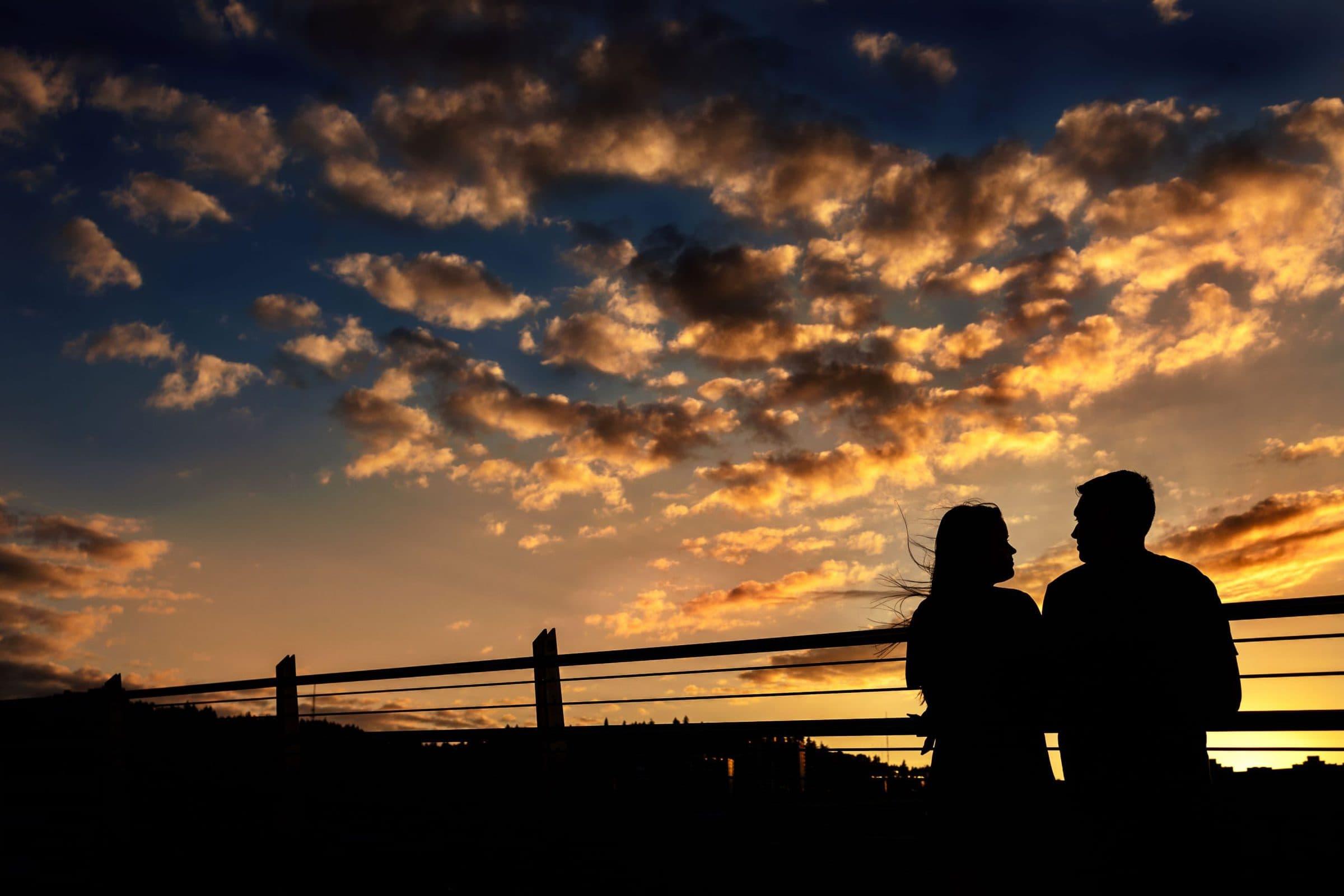 A beautiful sunset moment for a couple during their Tilikum Bridge engagement photos