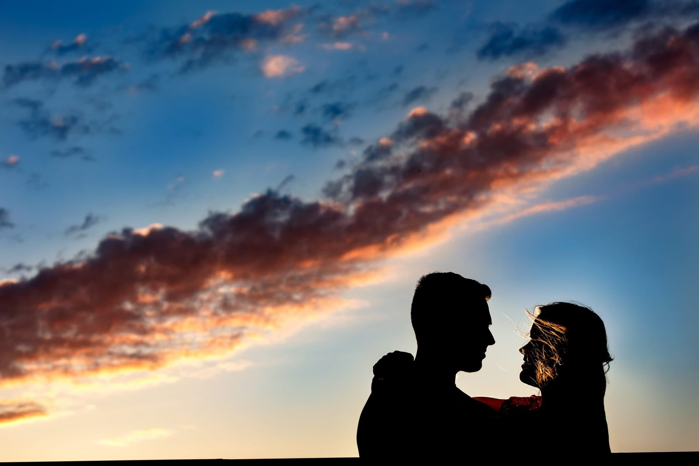 A gorgeous colorful sky with a couple embracing for their Tilikum Bridge engagement photos