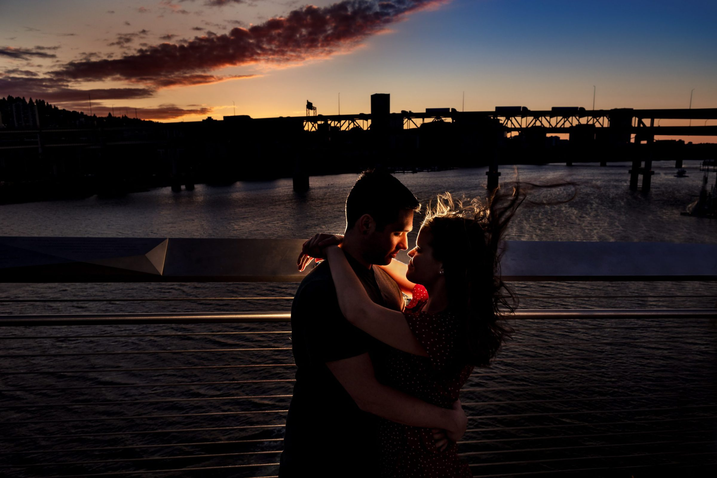 A beautifully lit and romantic photo of a couple at sunset in Portland Oregon for their Tilikum Bridge engagement photos