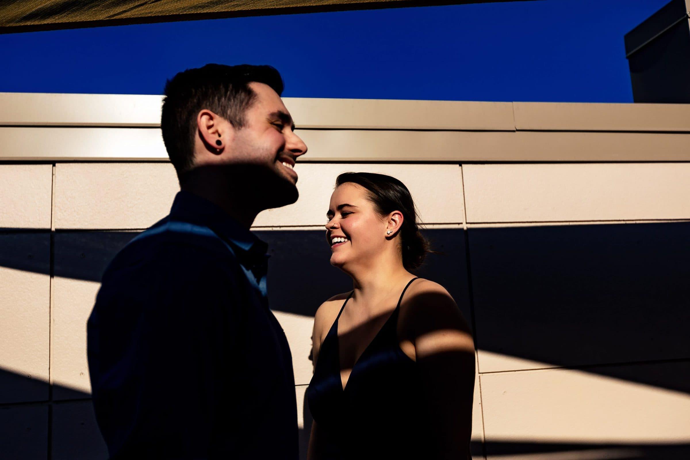 A couple enjoying the sun and dramatic shadows for their Tilikum Bridge engagement photos